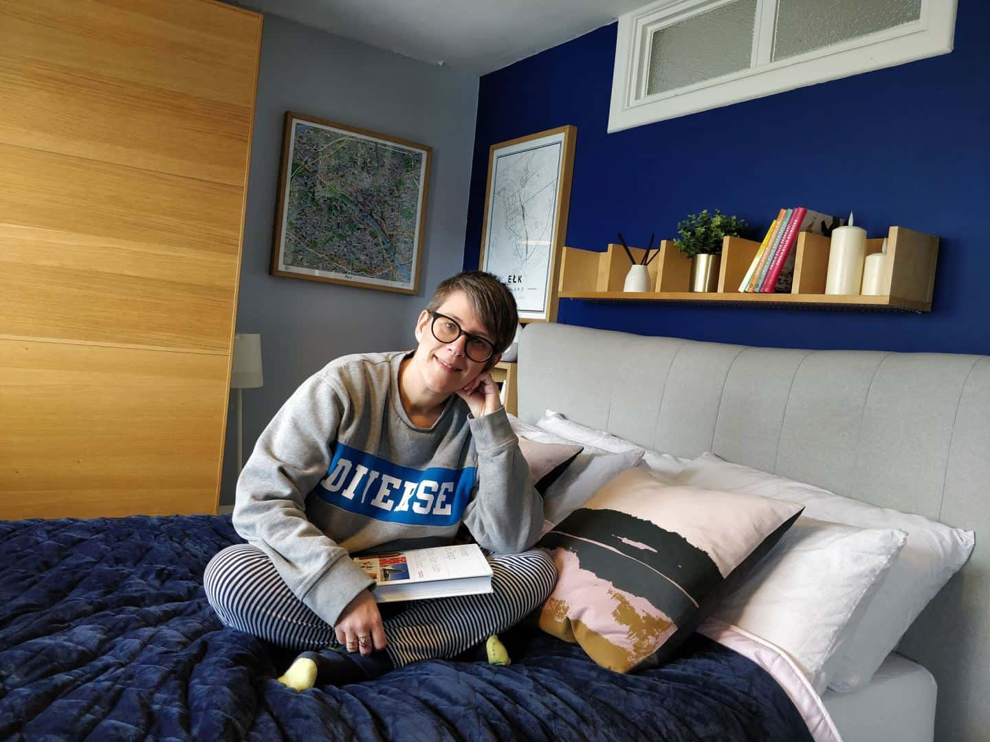 World Sleep Day 2020-5 Ways to Improve your Sleep. Woman sitting on a bed with a book.