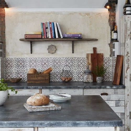 Reclaimed or antique tiles on a kitchen floor and used as a splashback - Maitland & Poate