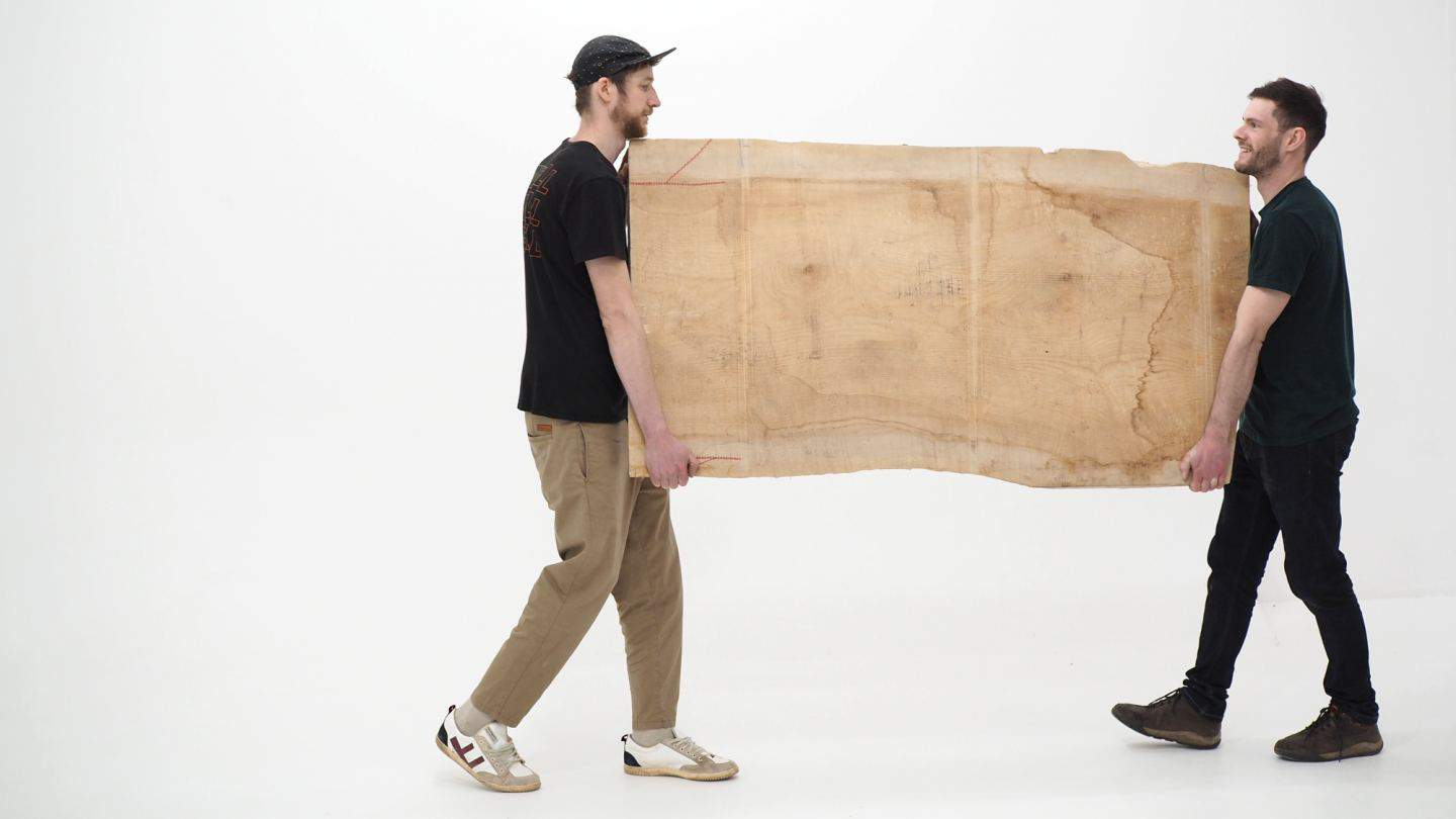 Oli and Josh of Forge Creative carrying a large piece of wood