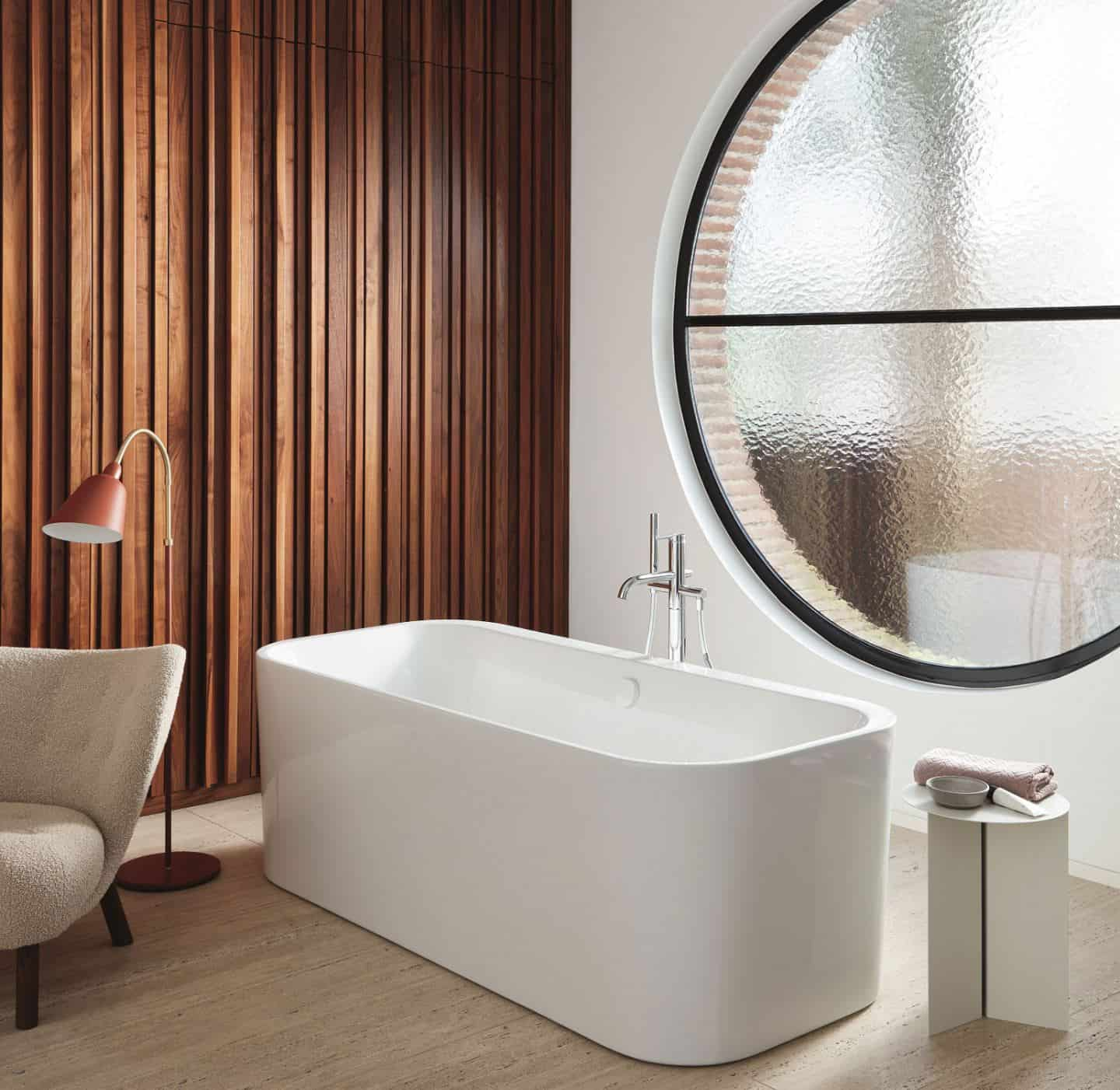 Duravit Happy D.2 Plus C-Shaped bathroom range. Freestanding bathtub in front of a large circular window.