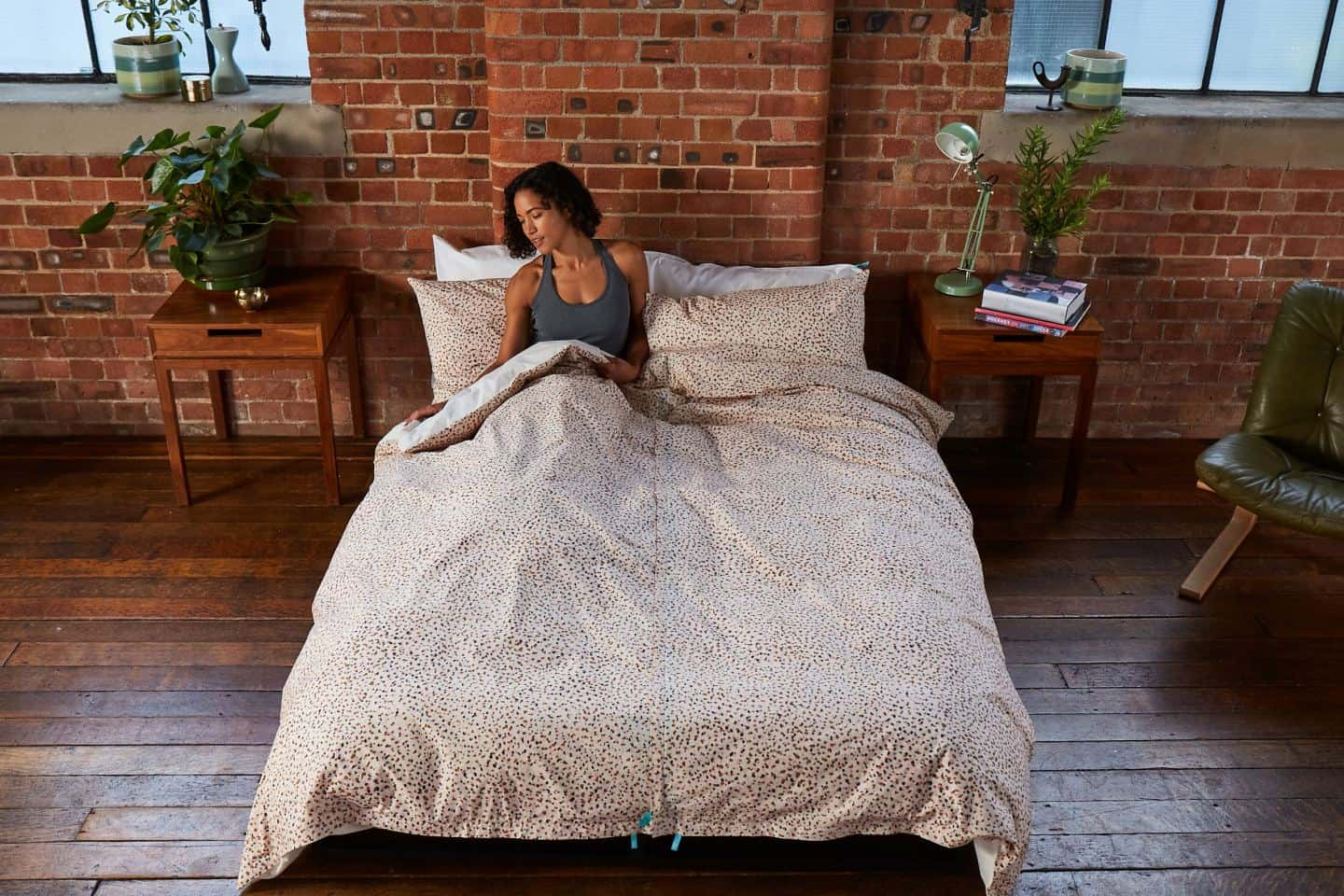 Koa revolutionary duvet cover. A woman in bed in an industrial style loft bedroom. The easy way to change a duvet cover
