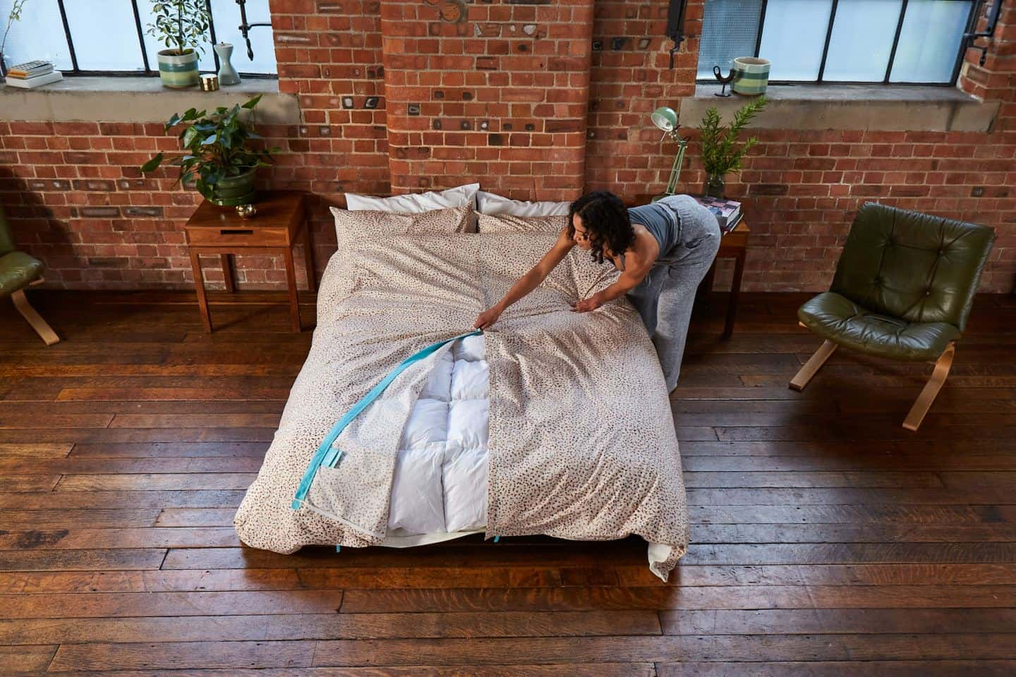 Koa revolutionary duvet cover shown in an industrial loft bedroom. A women zips up the central zip. The easy way to change a duvet cover