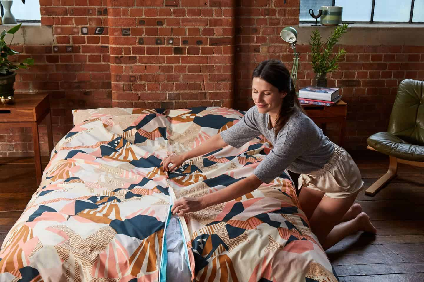 Koa revolutionary duvet cover. A woman closes the central zip once the duvet has been positioned inside. The easy way to change a duvet cover