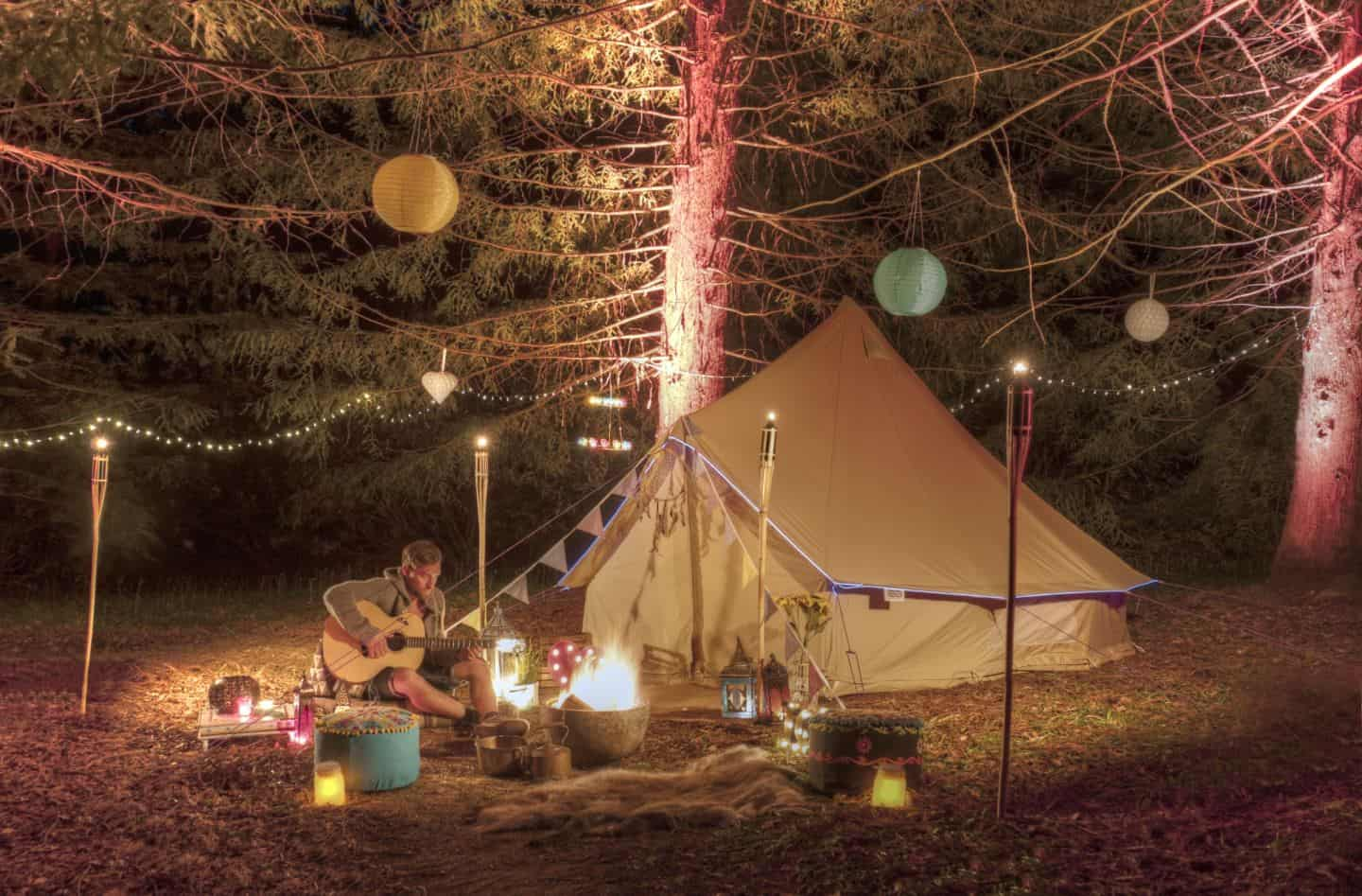 A man sat outside a tent in a woodland clearing playing guitar surrounded by tiki torches and paper lanterns hanging from trees.