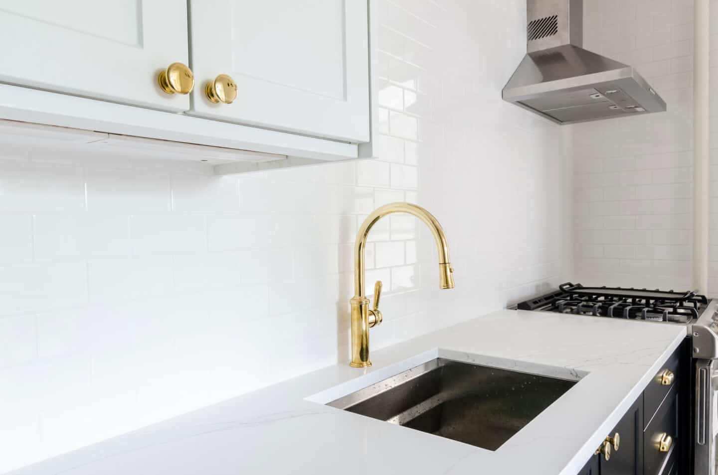 6 Easy Ways to Spruce Up Your Kitchen on a Budget - replace the tap. Image of a brass tap on a white countertop with white wall tiles behind.