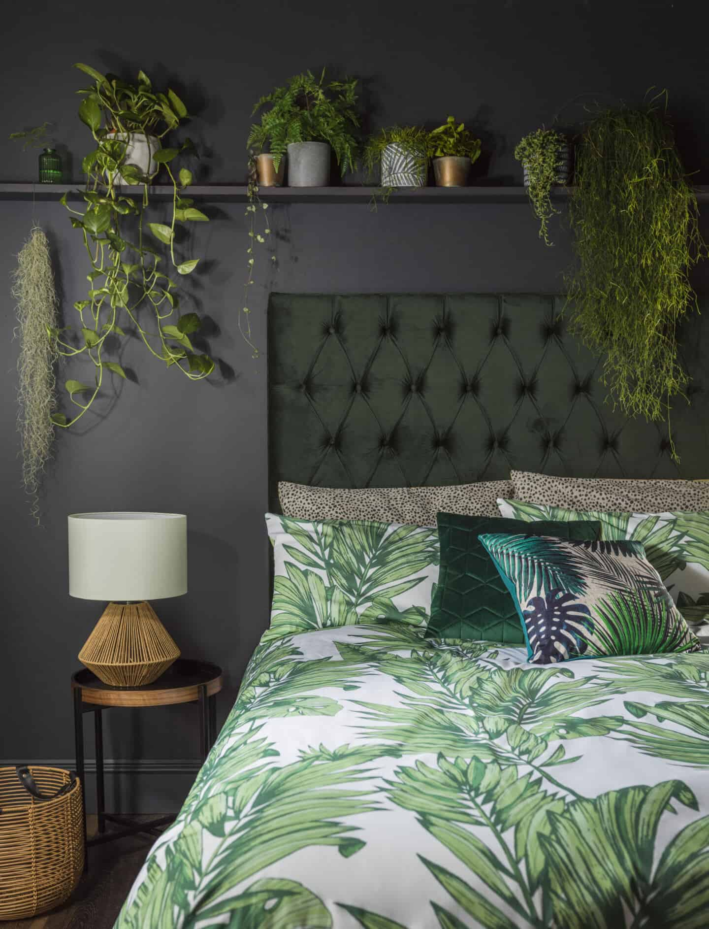 Botanist is a SS20 interiors trend by Very.co.uk that features nature in interiors. This bedroom features a plush velvet headboard, printed leafy bedding and lots of plants on a shelf above the bed