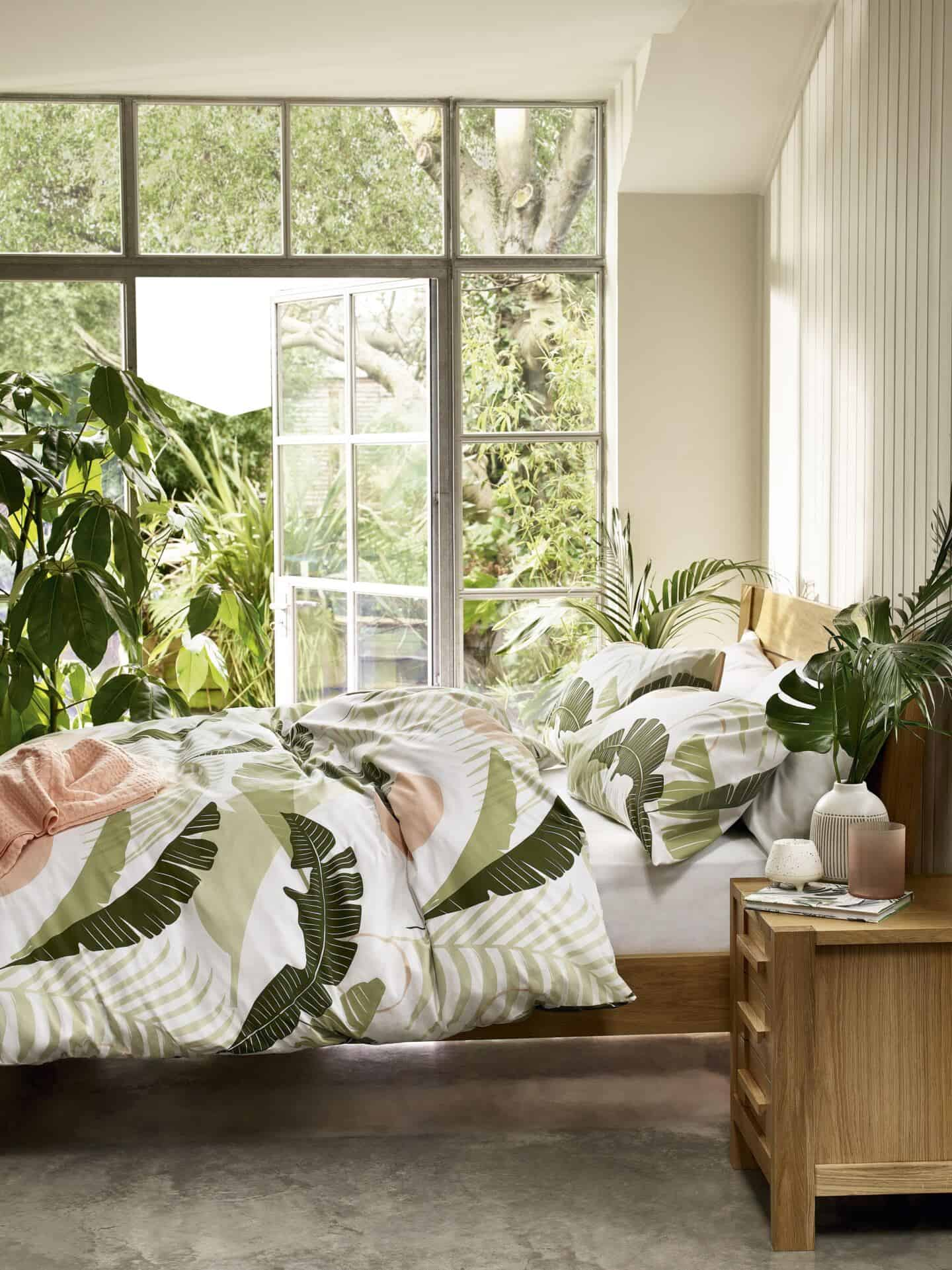 Nature in interiors. SS20 trend Botanical by M&S. Sonoma bedding on a wooden double bed in front of french doors with a garden outside
