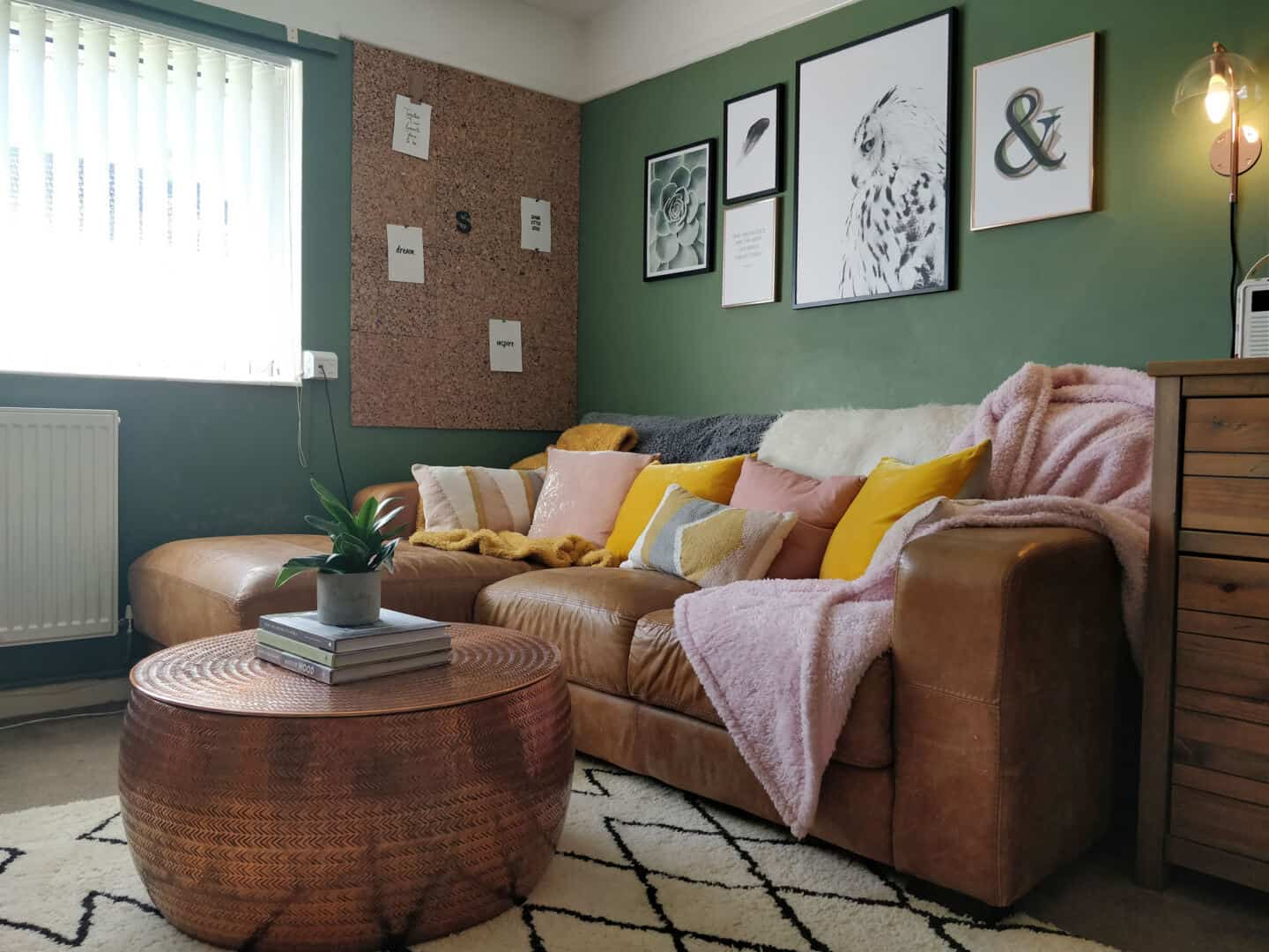 Autumn home updates with Habitat. A green living room featuring a brown leather sofa, copper coffee table and pink and yellow velvet cushions.