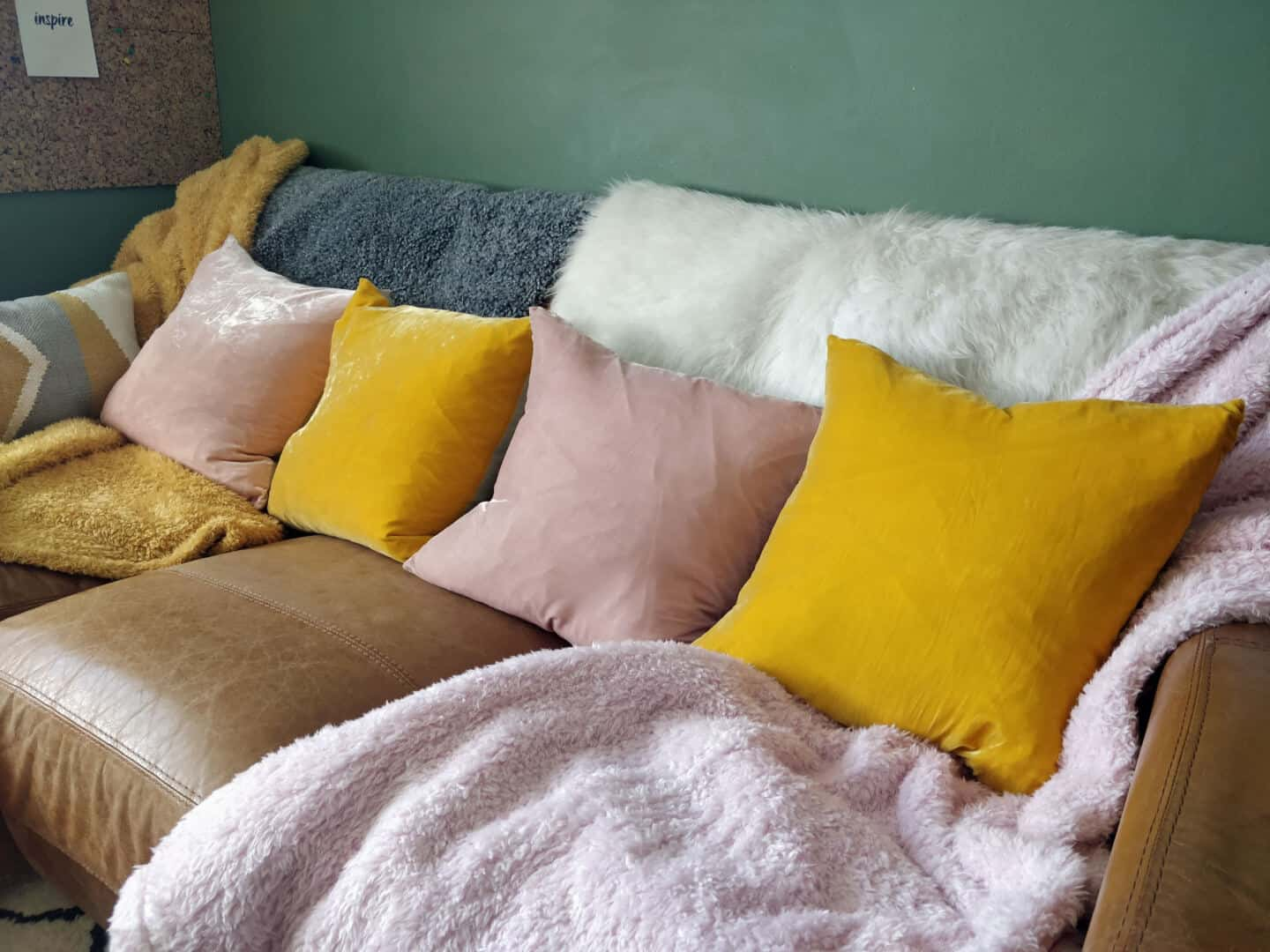 Autumn home updates with Habitat. A living room featuring a brown leather sofa and pink and yellow velvet cushions.