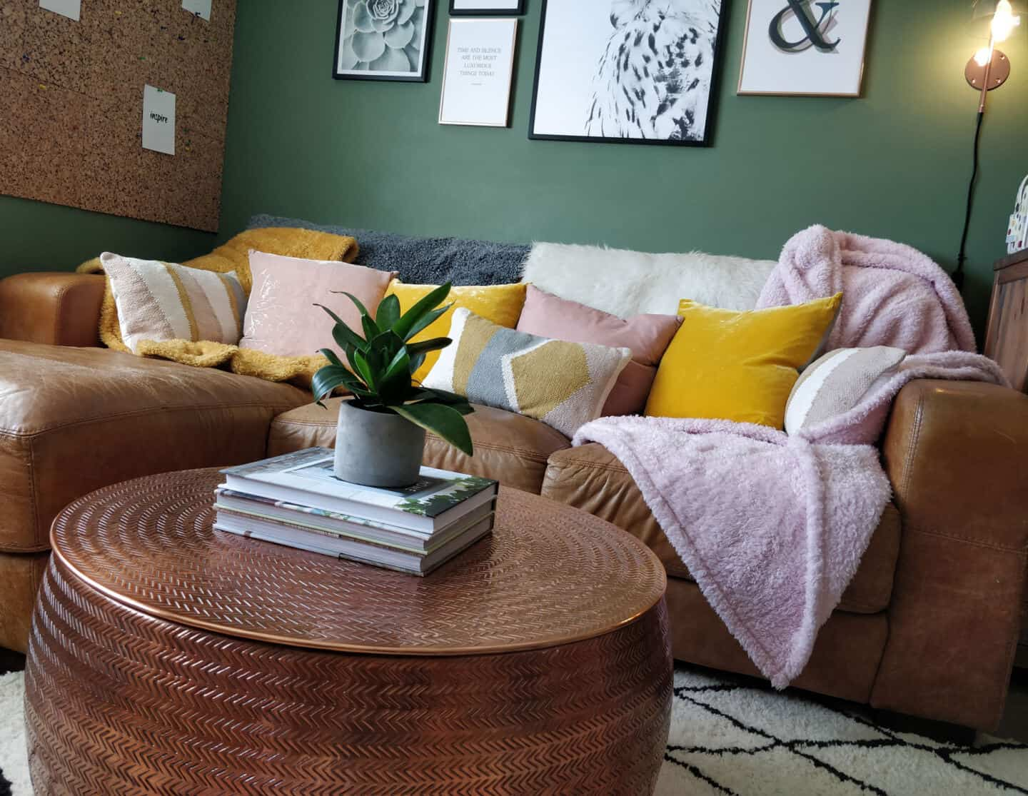 Autumn home updates with Habitat. A living room featuring a brown leather sofa, copper coffee table and pink and yellow velvet cushions.