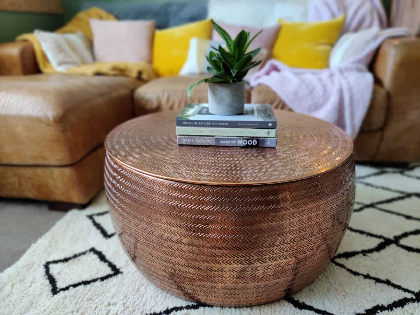 Autumn home updates with Habitat. A living room featuring a hand-etched copper coffee table on a berber rug.