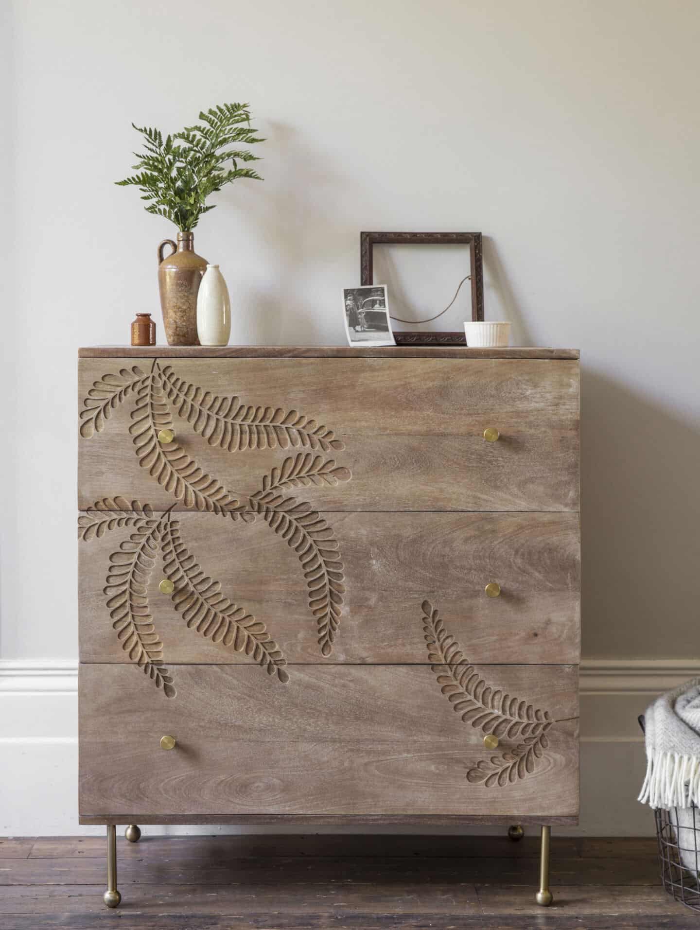 Bringing Natural Elements into the Home. A wooden chest of drawers with a large fern leaf etched into the surface