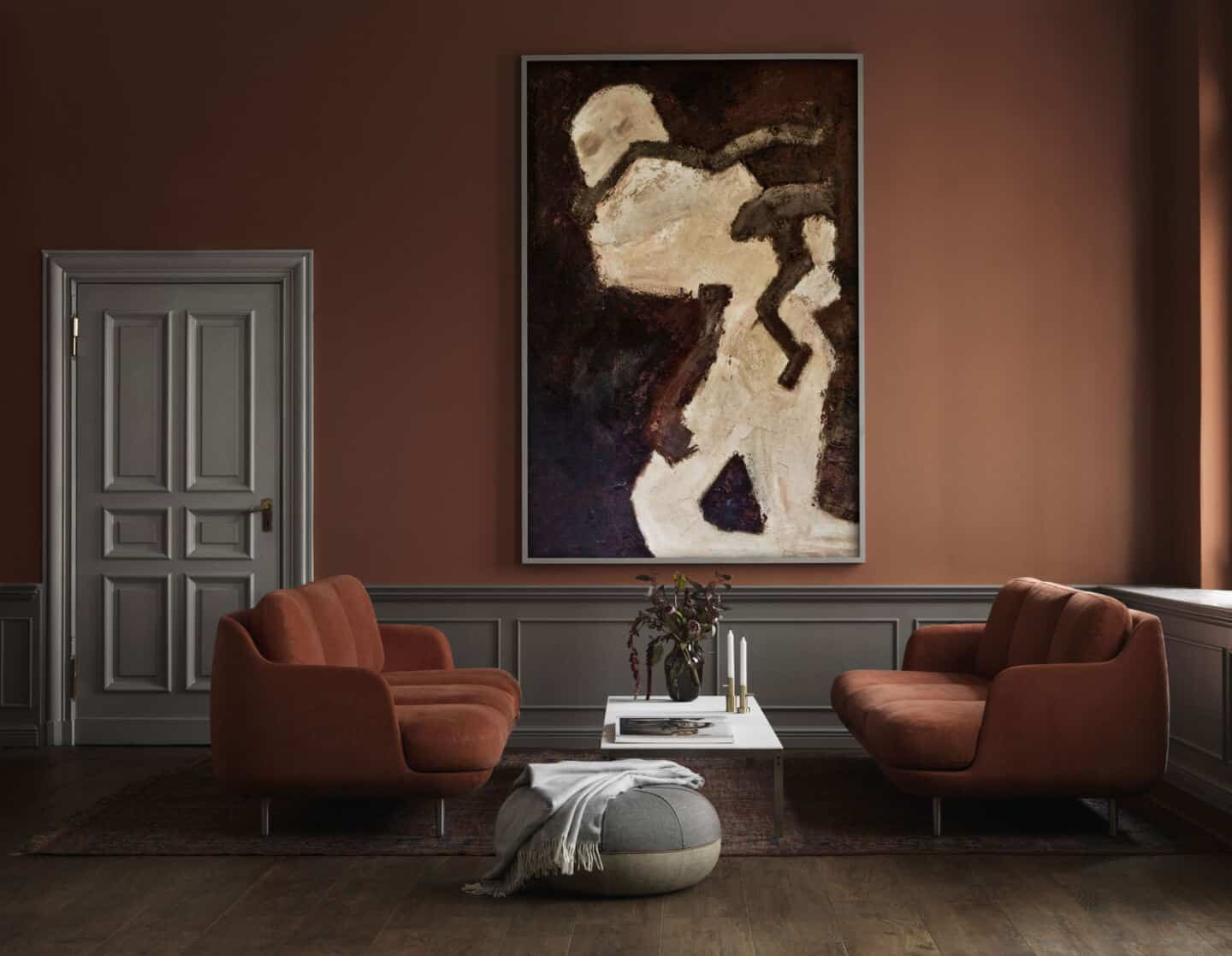Autumnal Hues in interiors - A living room set up featuring two sofas facing one another either side of a coffe table, with a large piece of abstract artwork hung on the wall behind.