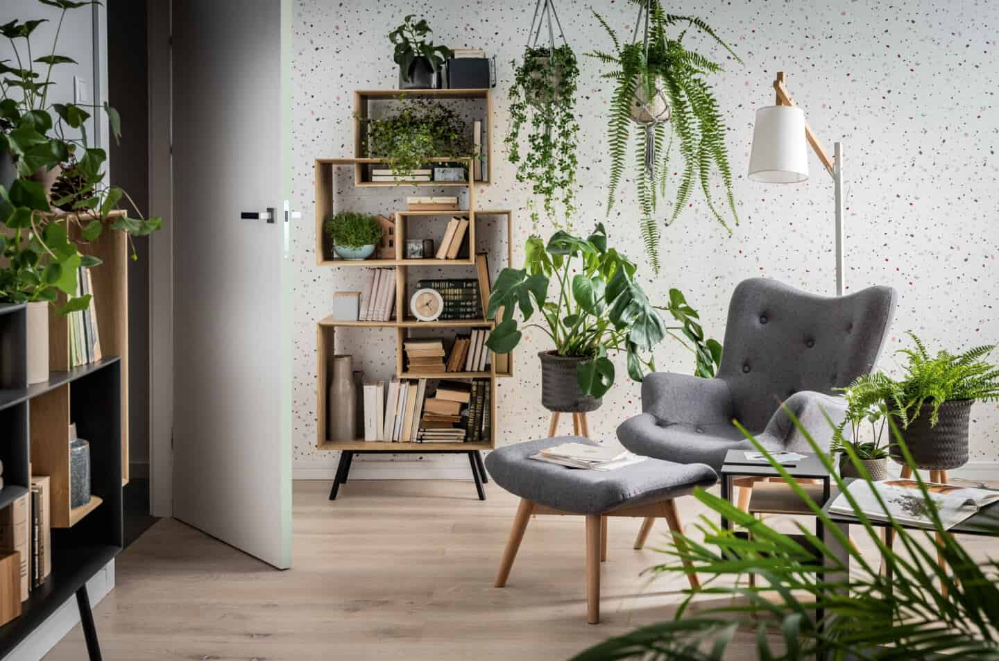 Bringing Natural Elements into the Home. Living room and  featuring a grey chair and footstool surrounded by plants.
