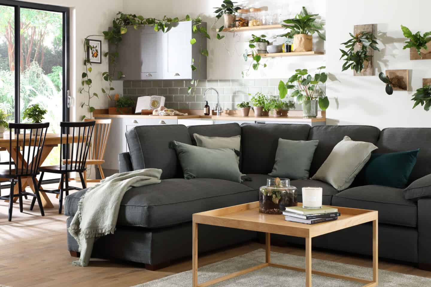 Bringing Natural Elements into the Home. Living room and  featuring a grey sofa with a kitchen dining space behind. The room is full of plants.