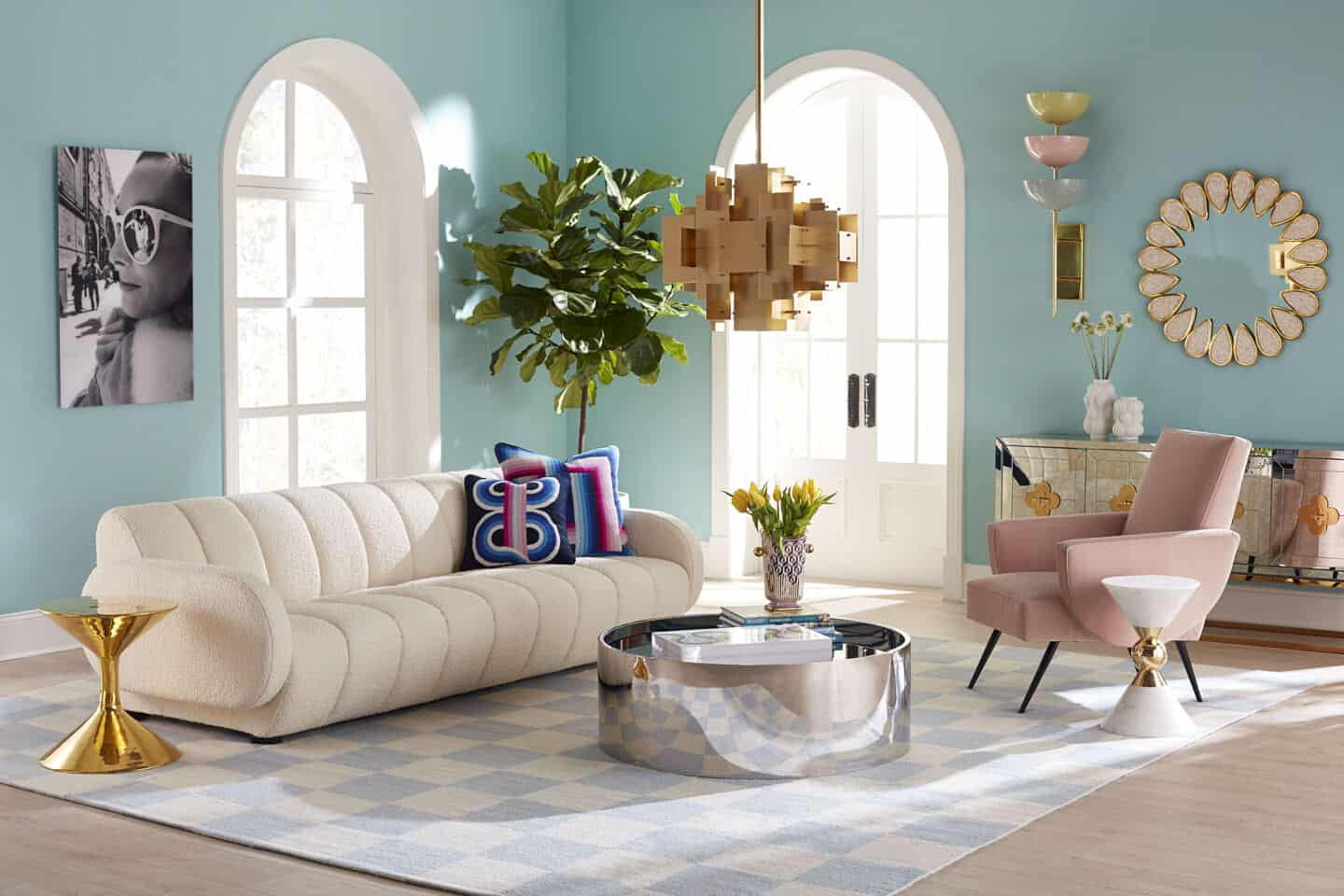 Jonathan Adler's Brigitte sofa in bouclé texiles in a living room setting. The livingroom is in pastel hues and the sofa is on a chequered rug
