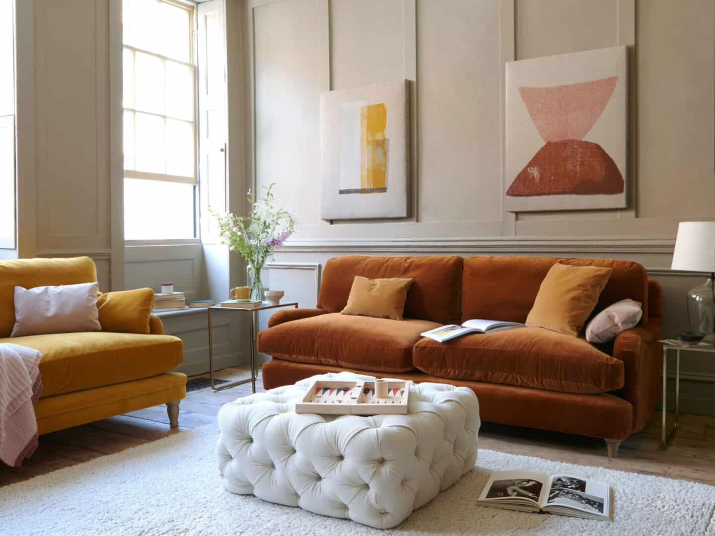 Autumnal Hues in interiors -Loaf Jonesy Sofa in Praline with abstract artwork on the wall behind and a white cushioned pouffe in front