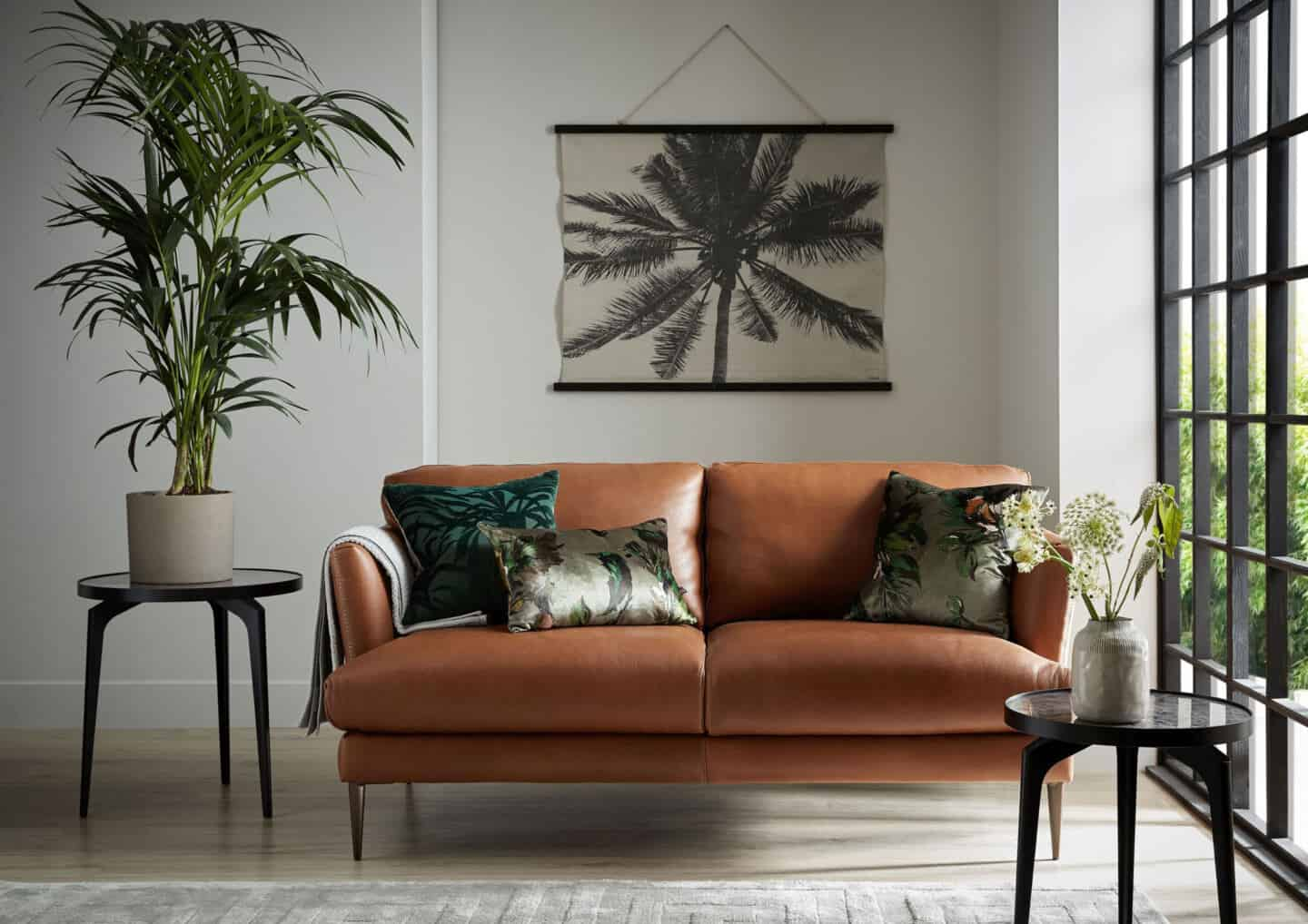 Bringing Natural Elements into the Home. Living room and  featuring a brown leather sofa with botanical cushions. A botanical wall hanging is on the wall behind and views through the window.