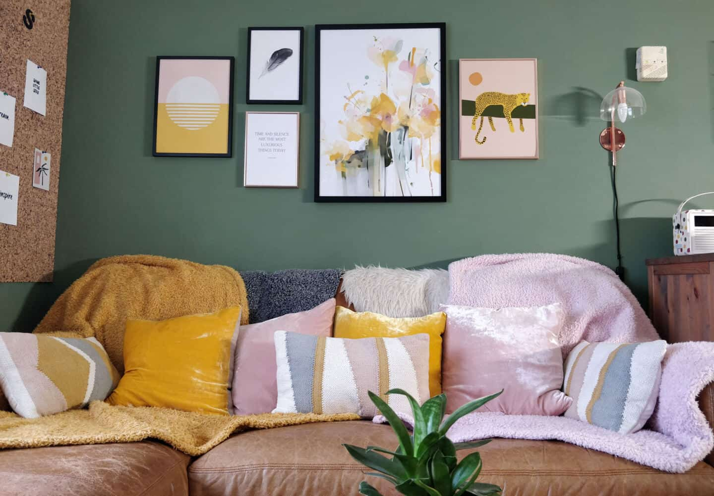 Pink & yellow artwork inspired by Travel from Greenlili hung on a moss green living room wall above a leather sofa covered in pink & yellow throws and cushions