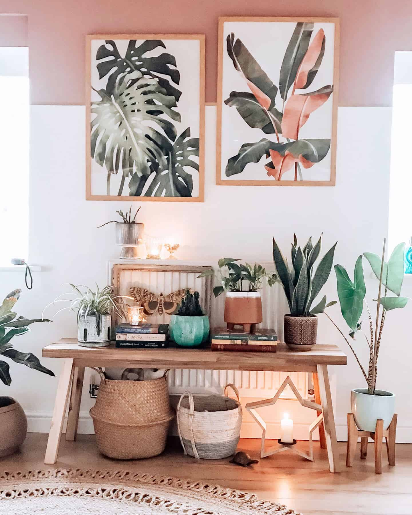 Botanical artwork inspired by Travel from Greenlili hung on a white and pink wall above a wooden bench covered in plant pots