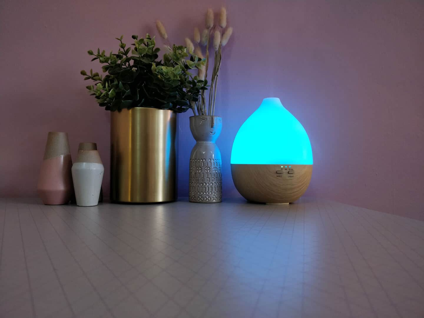Give your home a spring spruce up by adding scent. An aroma diffuser with light sits on a table next to plants and little vases.