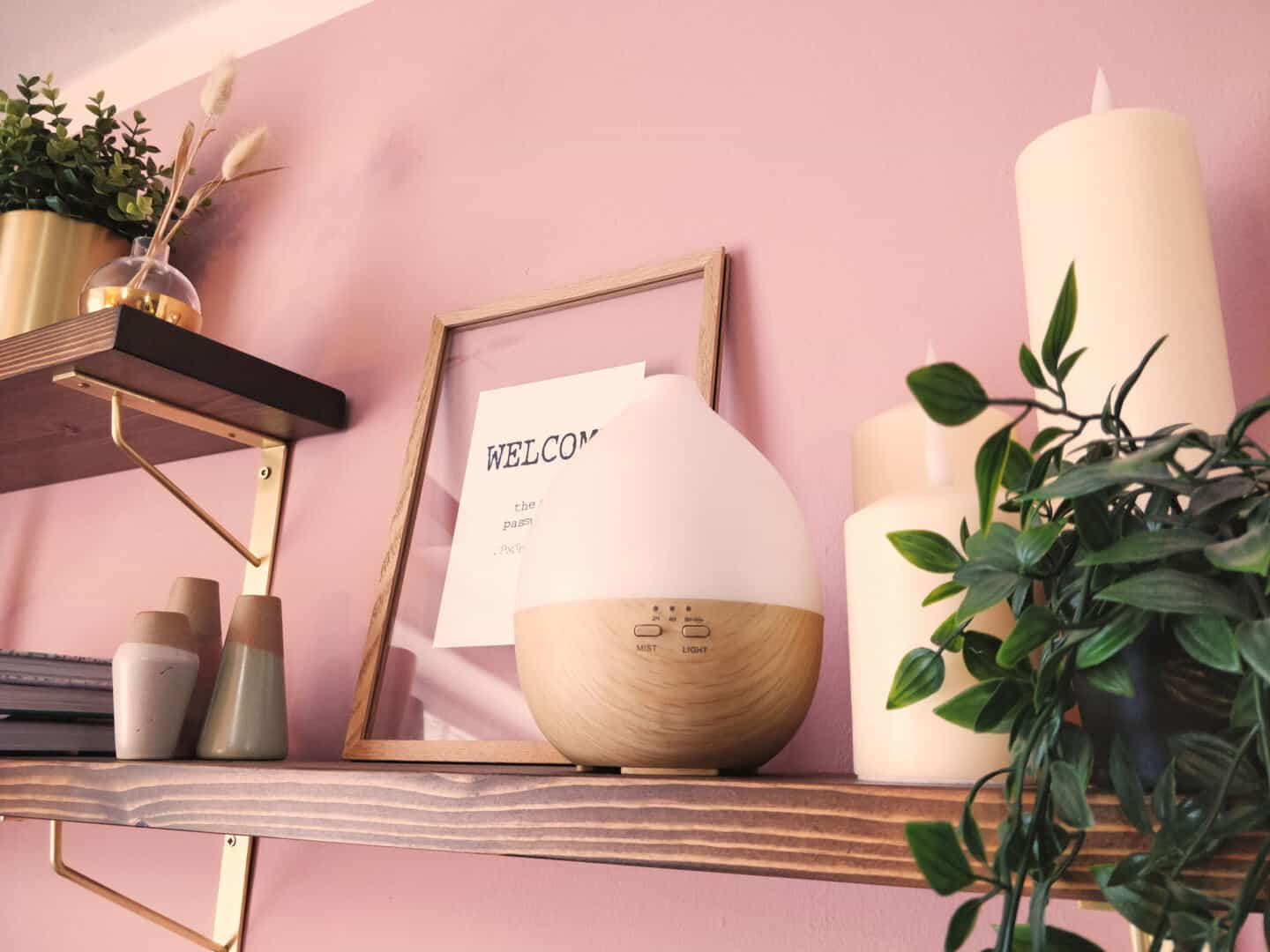Smellacloud aroma diffuser on a shelf with candles, plants and accessories