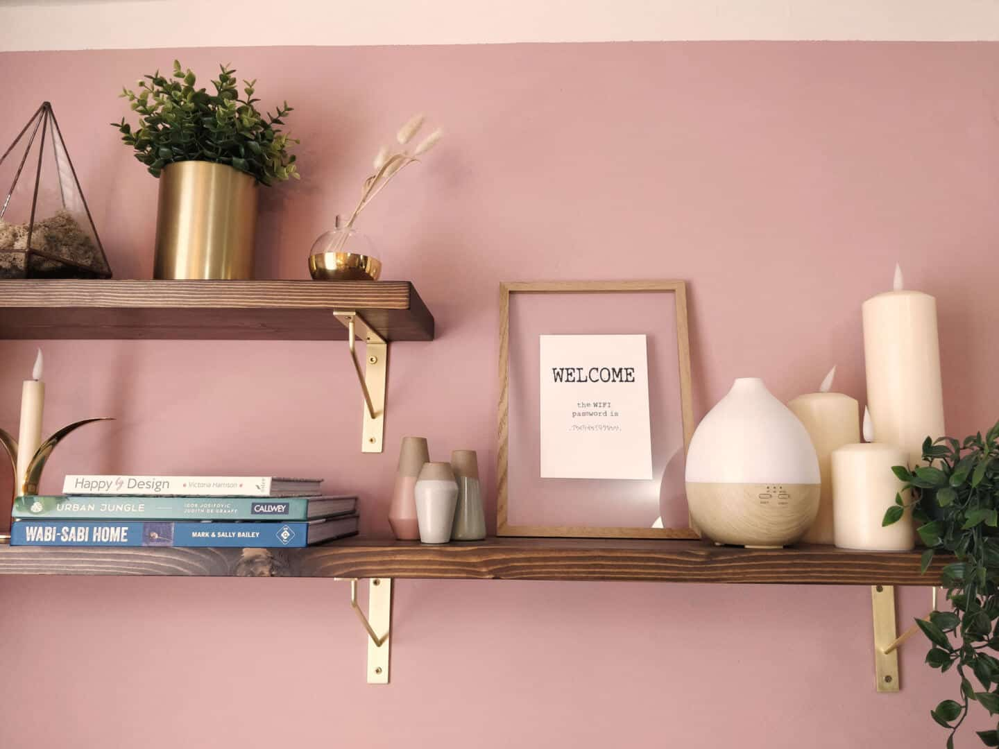 A shelf full of plants, candles, books and interior accessories
