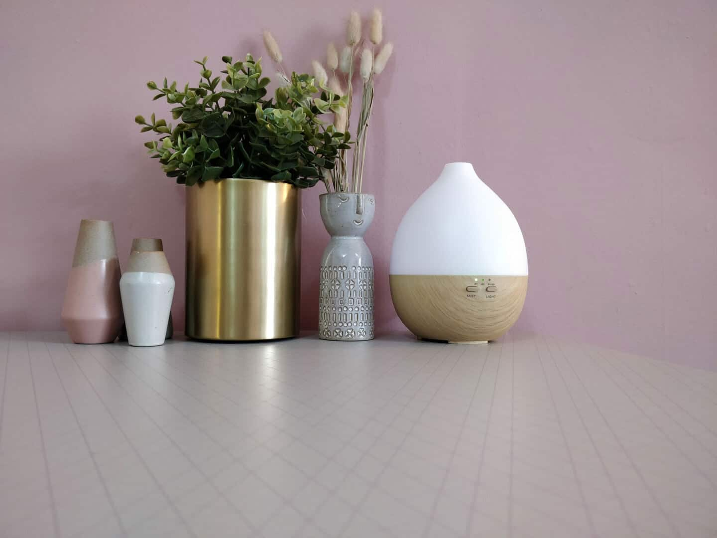 Smellacloud aroma diffuser on a table with plants and vases