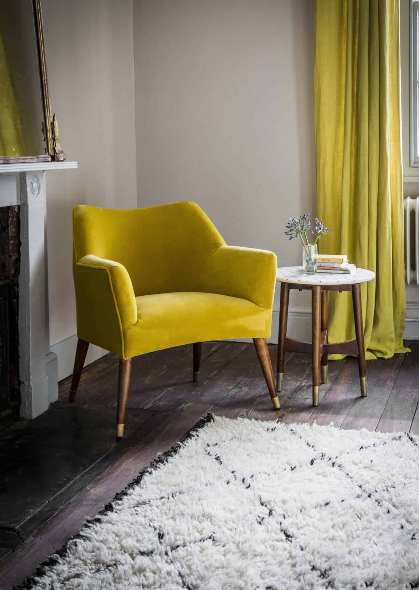 Pantone Colour of the Year 2021 - Illuminating. The colour psychology behind using yellow in interiors. A velvet yellow chair from Atkin & Thyme in the corner of a living room with a side table beside it and yellow curtains behind