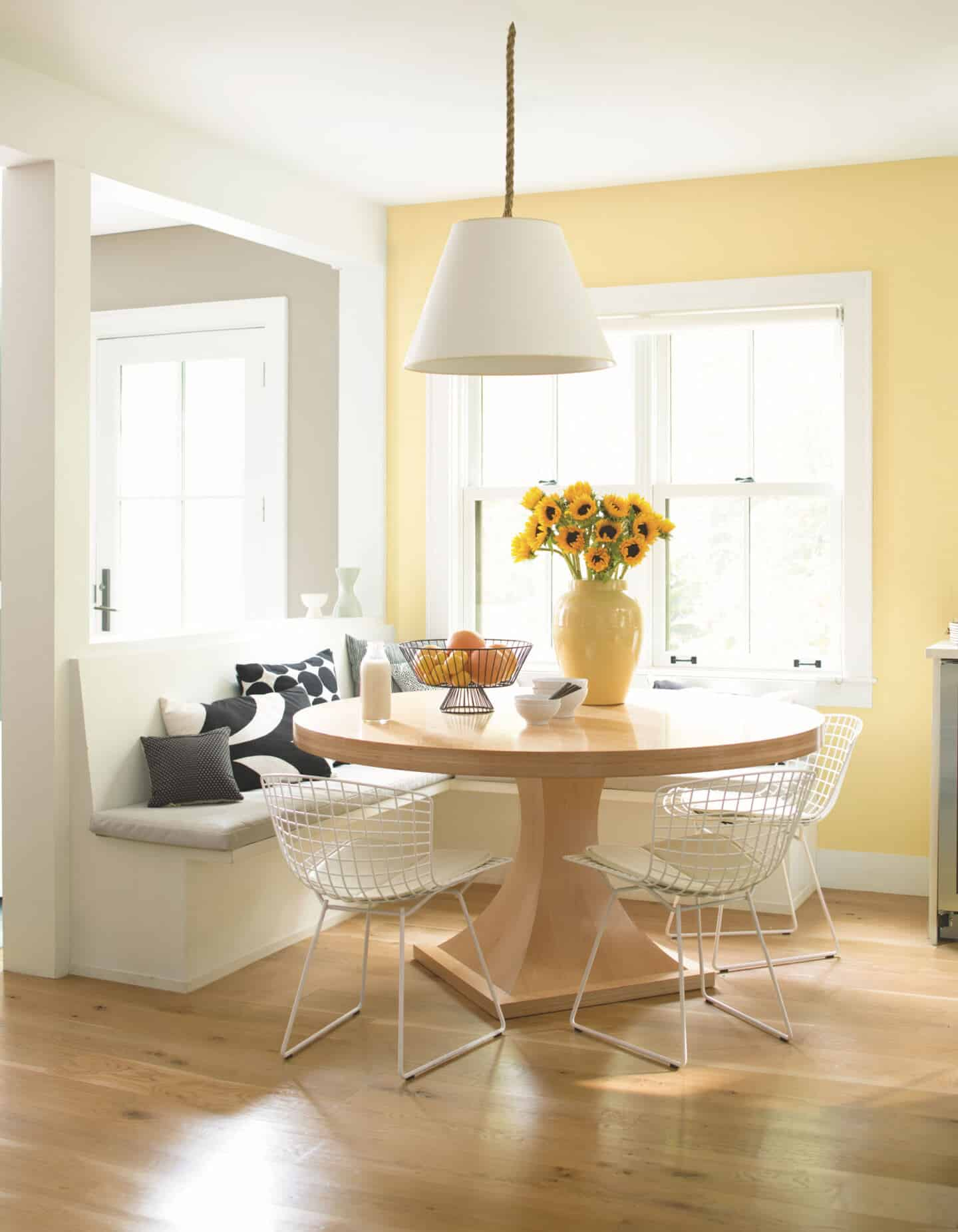 Pantone Colour of the Year 2021 - Illuminating. The colour psychology behind using yellow in interiors. A dining table in front of bench seating with a window behind. Wall painted in yellow paint from Benjamin Moore