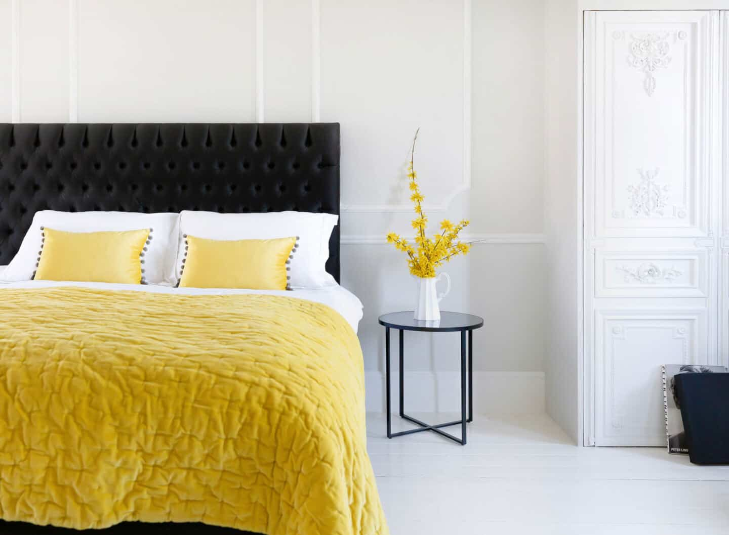 Pantone Colour of the Year 2021 - Illuminating. The colour psychology behind using yellow in interiors. A yellow bedspread and yellow cushions from The French Bedroom company on a bed in a white room
