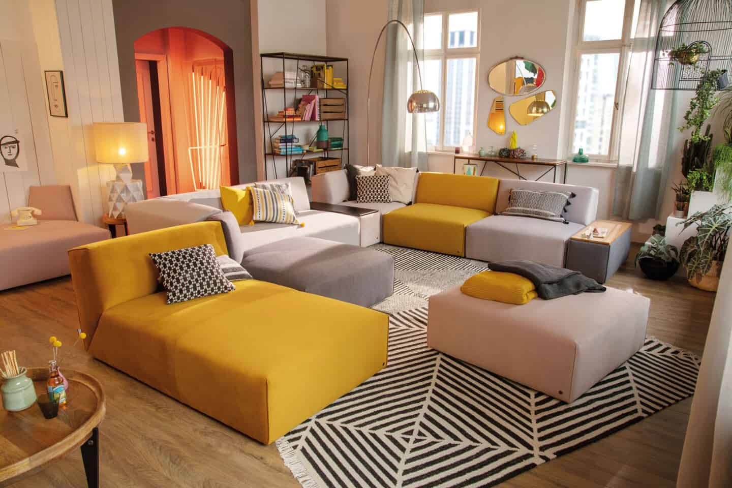 Pantone Colour of the Year 2021 - Illuminating. The colour psychology behind using yellow in interiors. A modular sofa from Tom Tailor Home with sections in yellow and grey in a living room