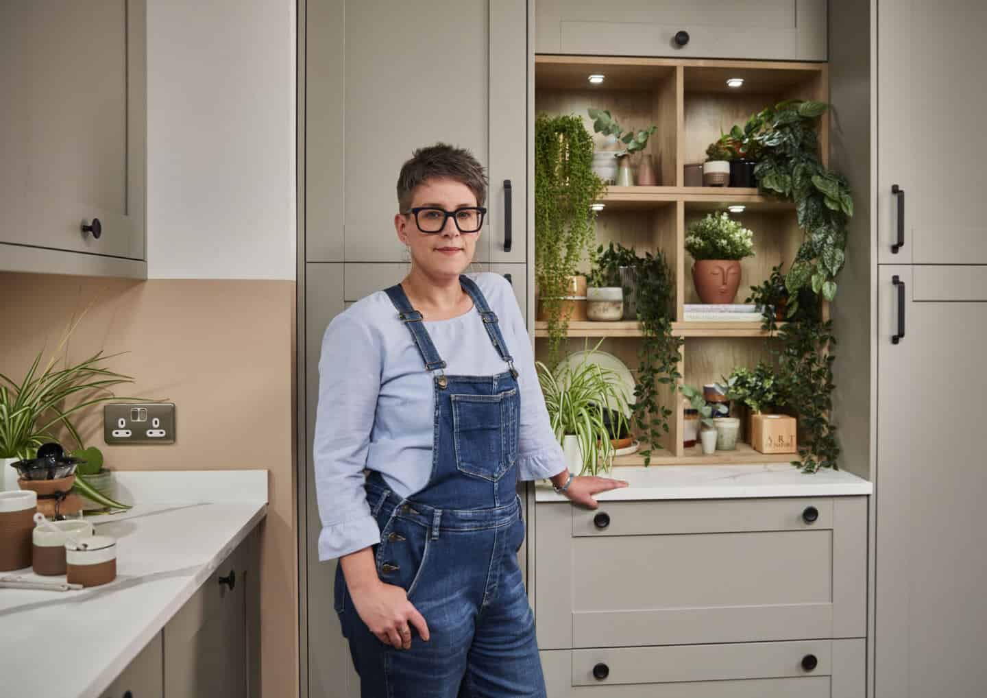 Award-winning Interior Design Blogger Stacey Sheppard stood in the Tatton Pebble Kitchen from Magnet Kitchens.