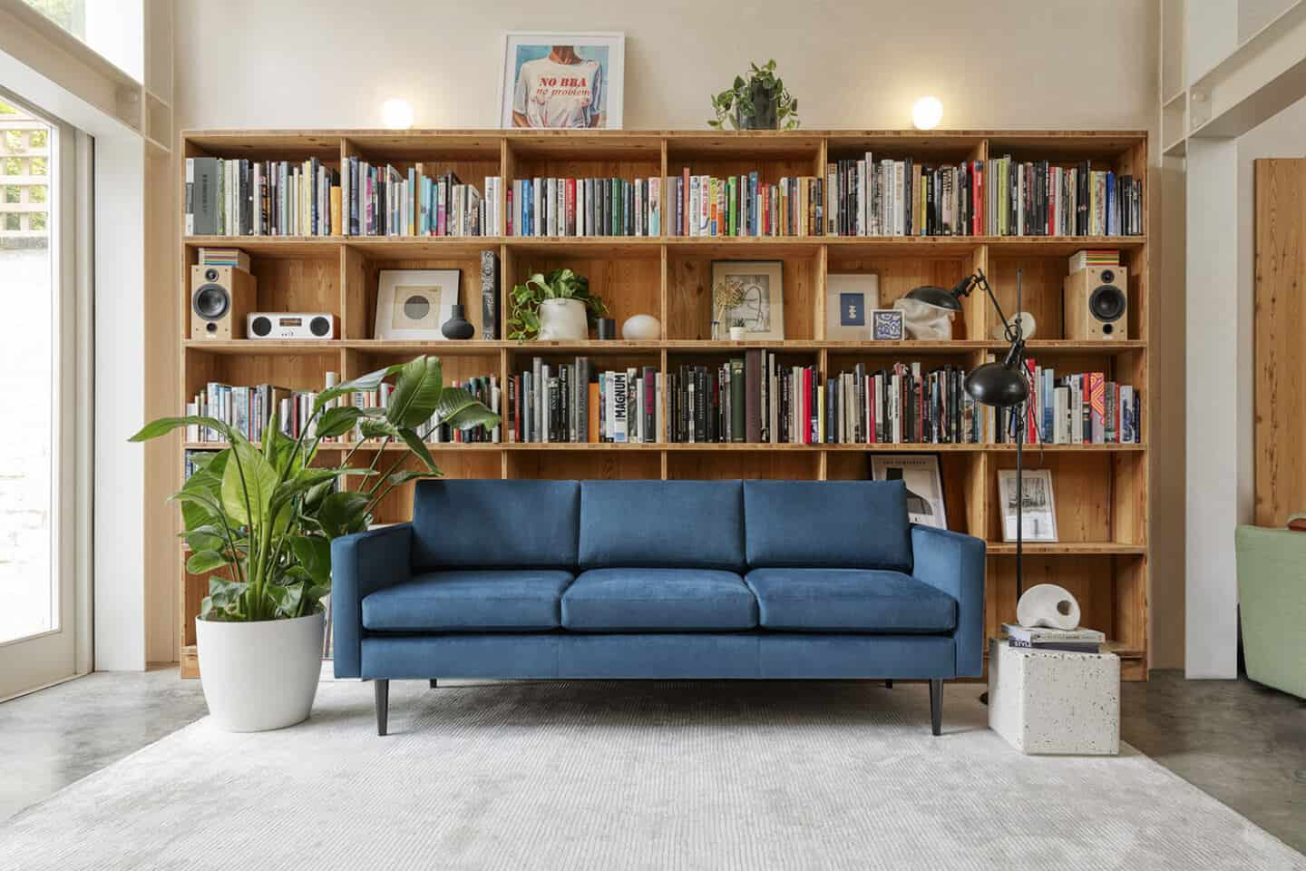 A blue sofa from Swyft Home on a grey rug, positioned next to a window and in front of a large wooden bookcase