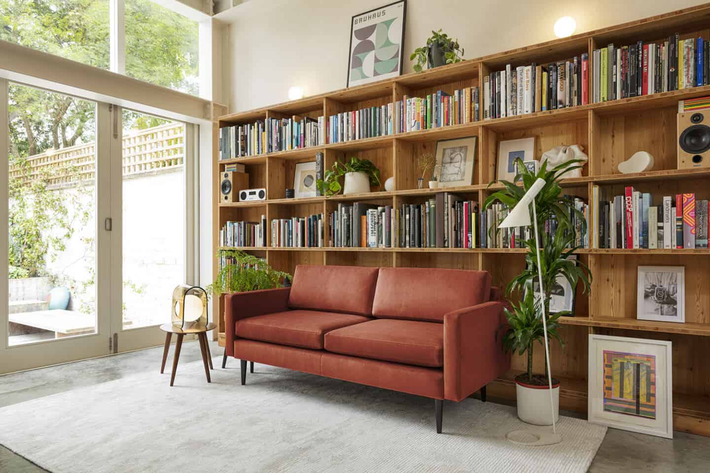 A red sofa from Swyft Home on a grey rug, positioned next to a window and in front of a large wooden bookcase