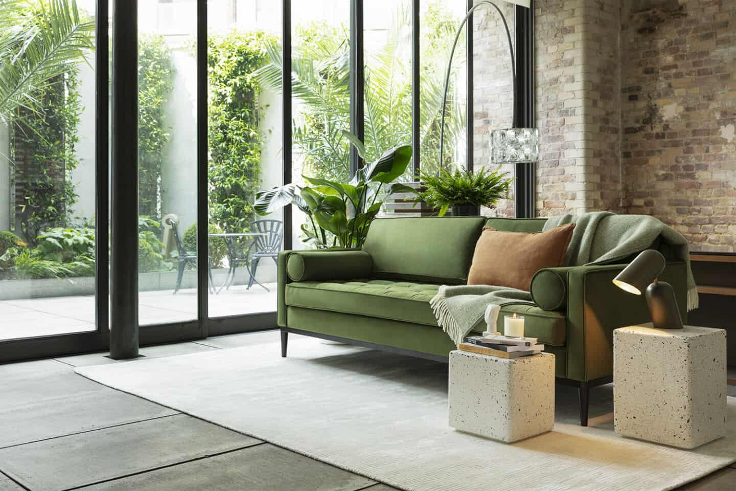 A green sofa from Swyft Home on a grey rug positioned next to a window with lots of plants outside and with a brick wall behind