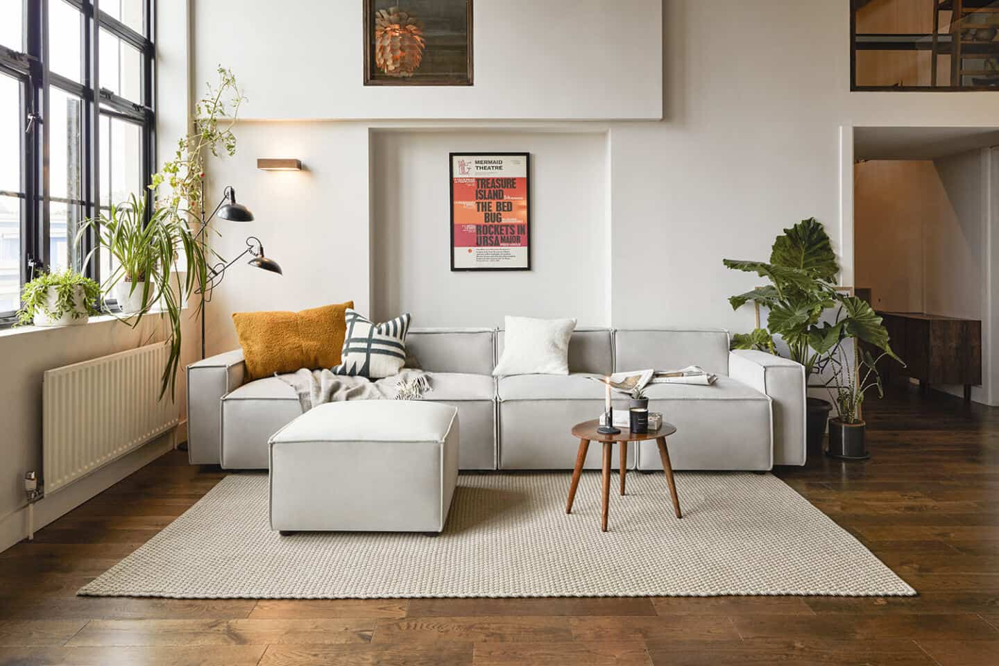 A grey sofa from Swyft Home on an oatmeal coloured rug, positioned next to a window and flanked by plants