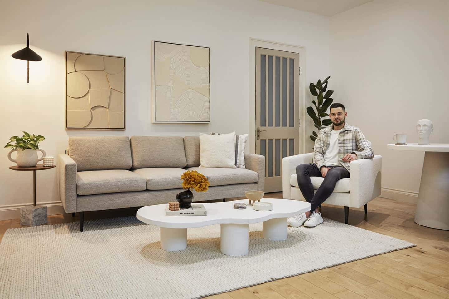 Interior designer Luke Arthur Wells sat on his new bouclé sofa collection designed in collaboration with Swyft Home
