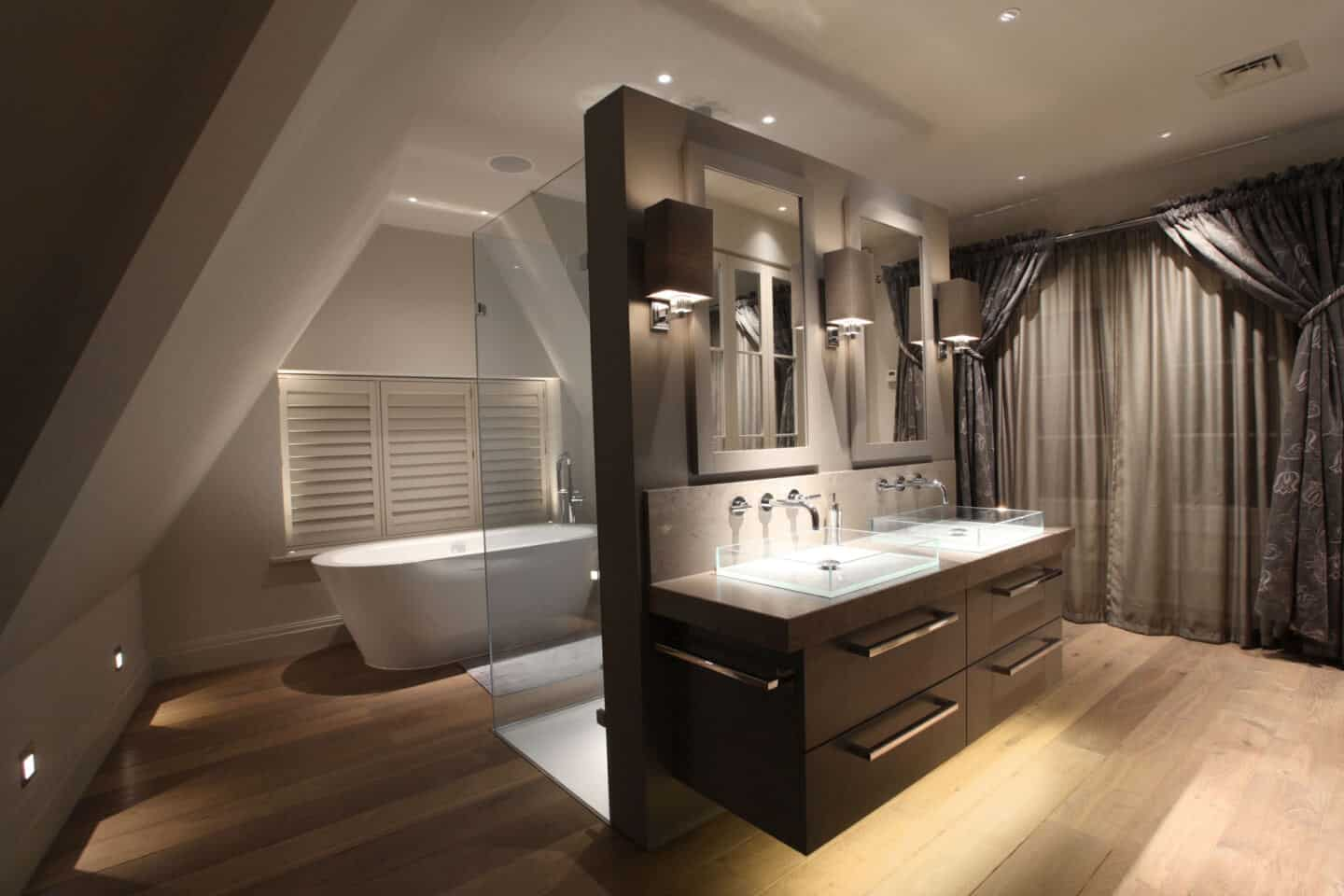 A luxury bathroom with double vanity, double shower and freestanding bath featuring layered lighting scheme by John Cullen Lighting.