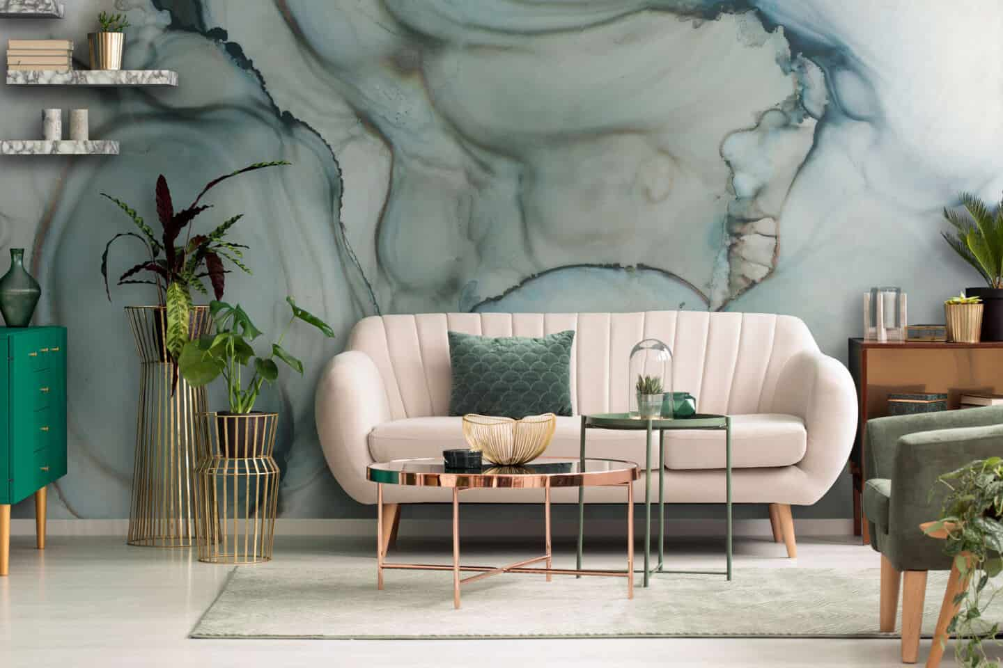 A white sofa on a neutral rug infront of a jade green abstract painted wall mural.