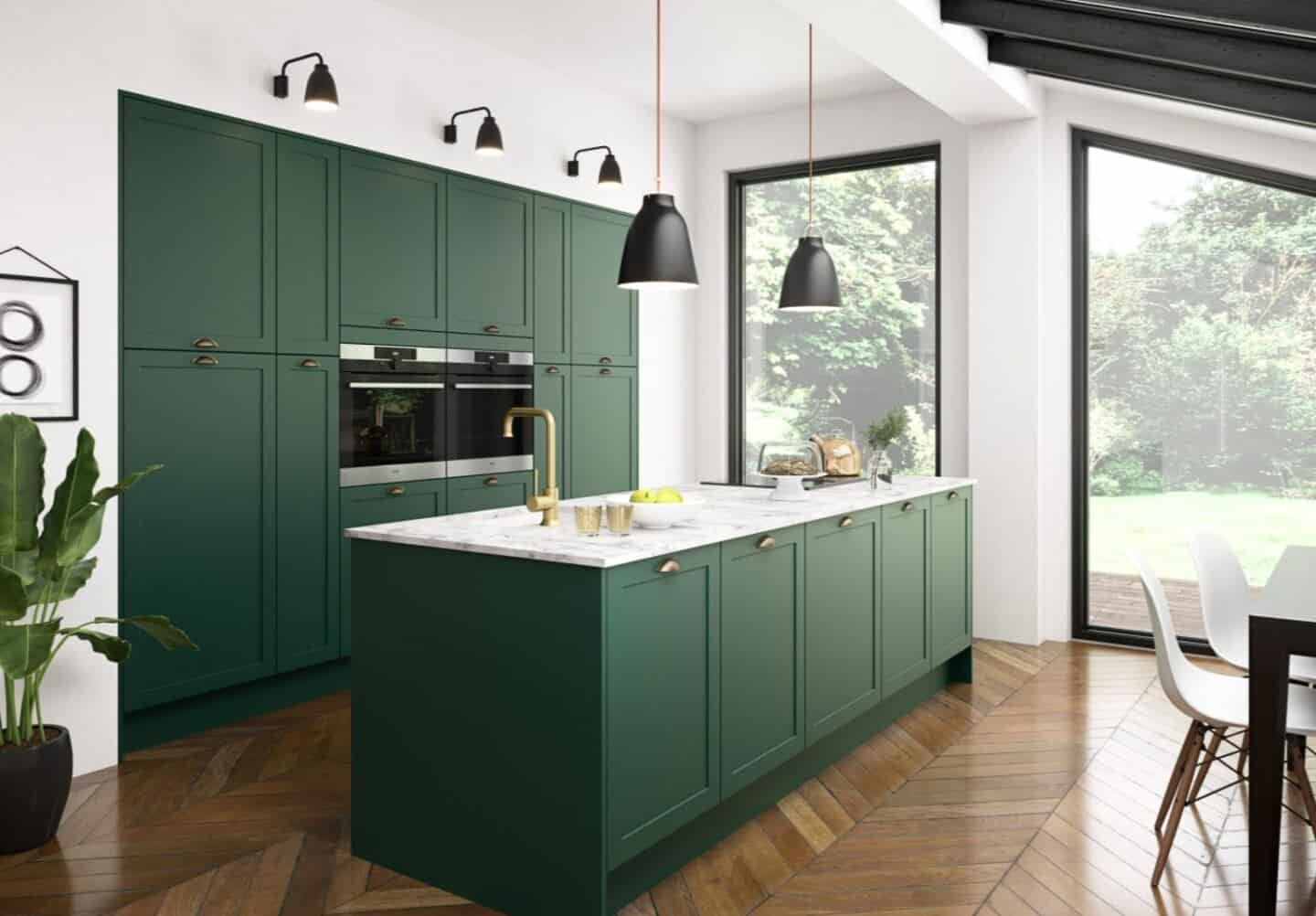 Magnet's Dunham Kitchen in Forest Walk. A deep dark green kitchen island with marble effect worktop in front of a run of green wall cabinets. Two large windows allow light to flood the kitchen