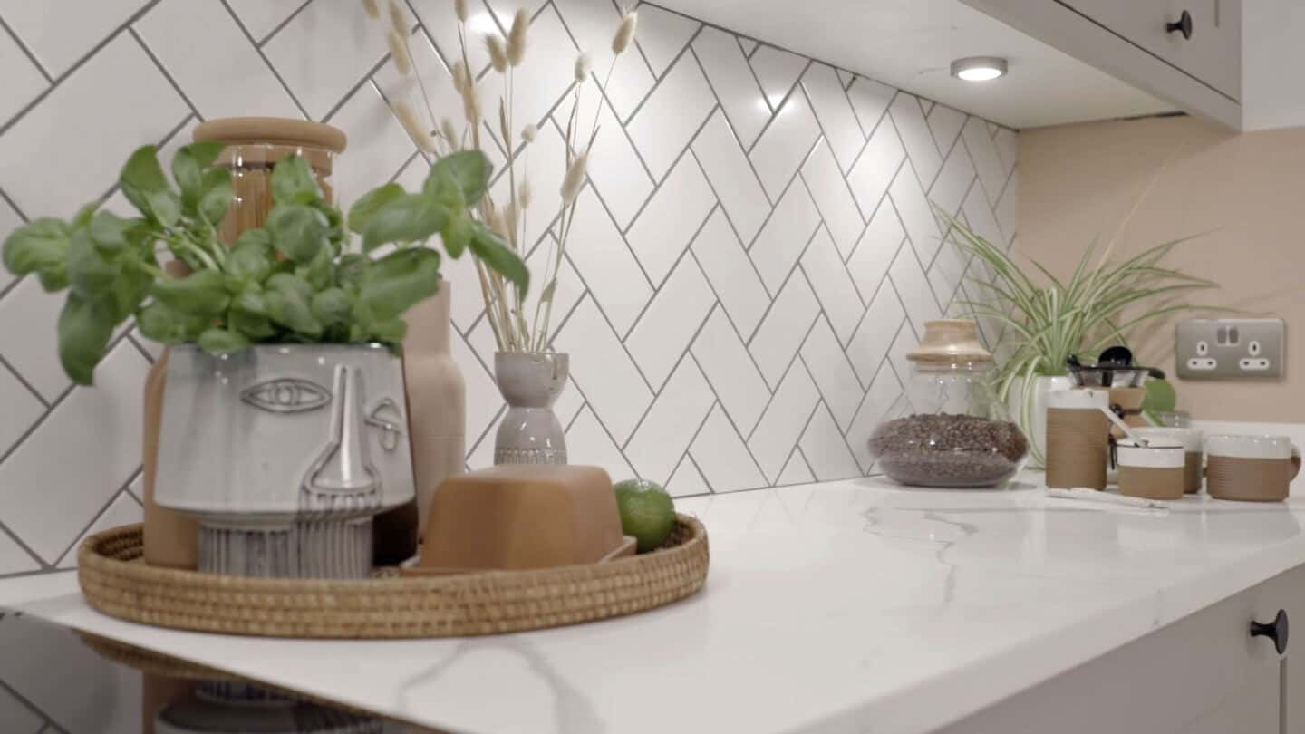 Biophilic kitchen designs provide a multi-sensory experience through natural materials and textures. Here kitchen accessories are displayed on a marble effect worktop.