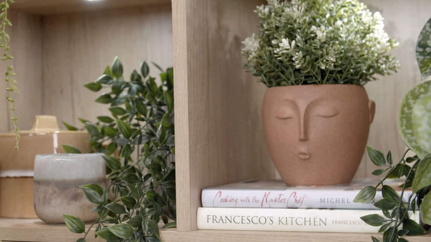A close up of built-in shelves in Magnet's Tatton kitchen full of plants and other accessories