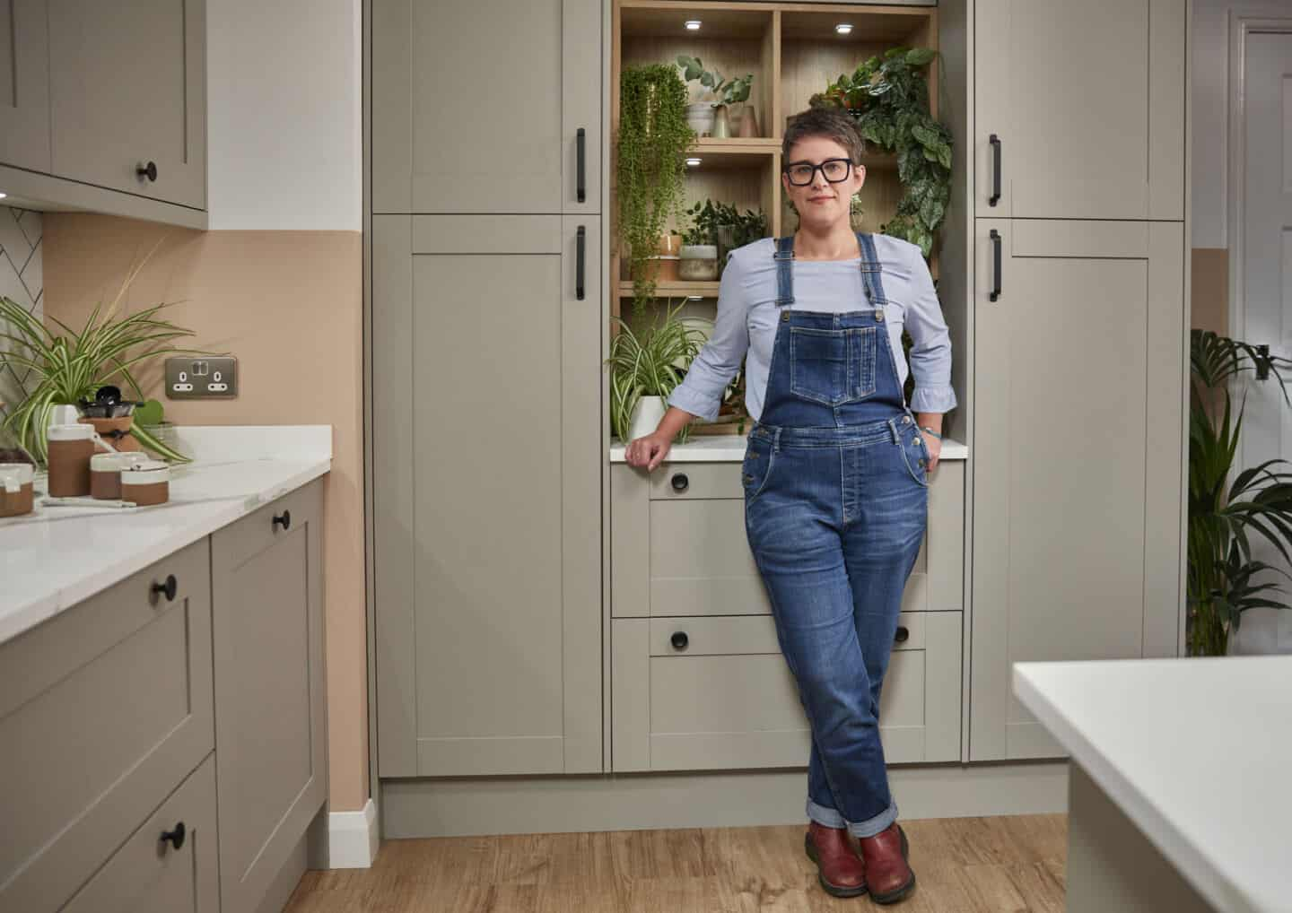 Blogger Stacey Sheppard stands in Magnet's Tatton Kitchen in front of built-in shelving full of plants. She shares tips for creating biophilic kitchen designs