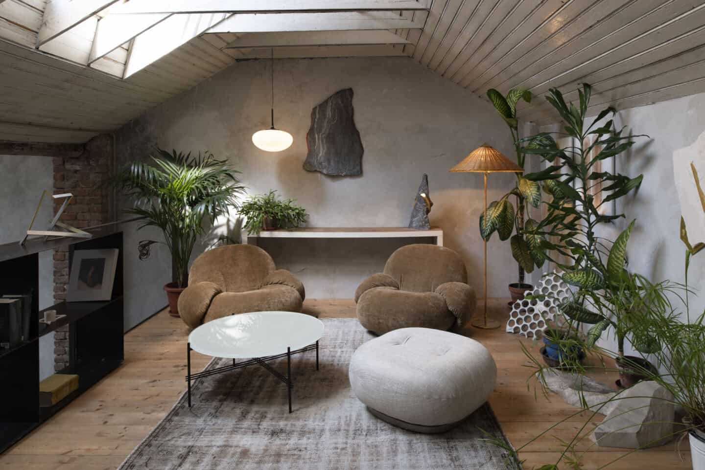 A couple of Pacha lounge chairs by Gubi sit in a loft room full of plants and natural textures. A perfect example of how to use organic shapes in interiors