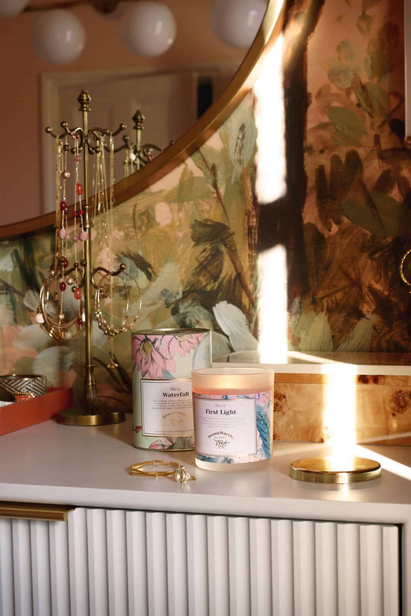 First Light, luxury eco-conscious scented candles by Swoon Worthy Scents on a chest of drawers next to a jewellry stand in the bedroom.