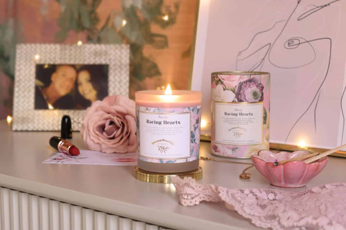 Racing Hearts, luxury eco-conscious scented candles by Swoon Worthy Scents on a chest of drawers in front of artwork and a photo of a couple.