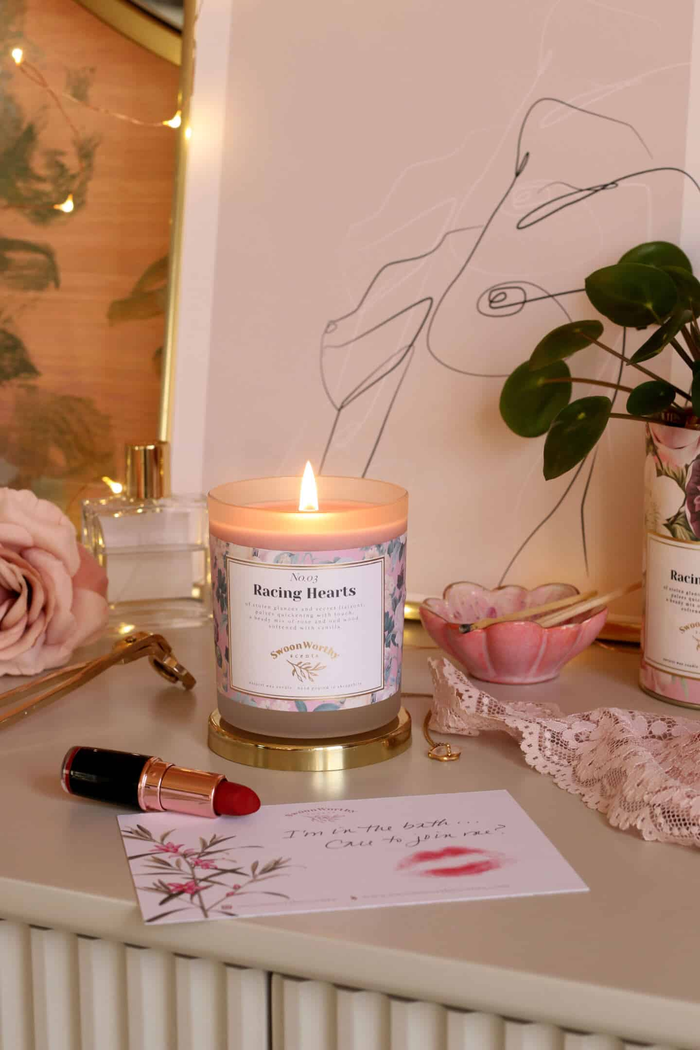 Racing Hearts, luxury eco-conscious scented candles by Swoon Worthy Scents on a chest of drawers in front of artwork and a bottle of perfume.