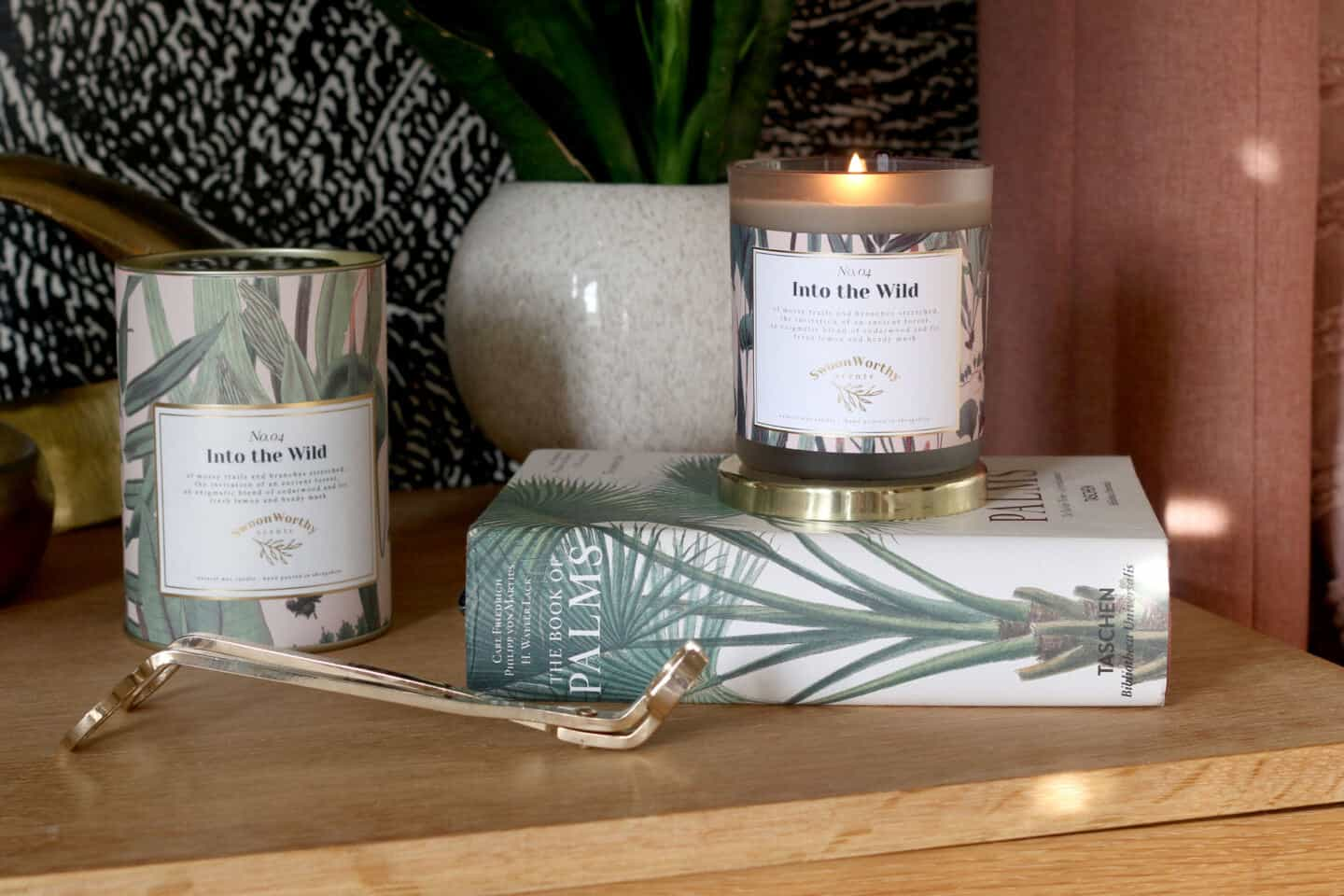 Into the Wild luxury eco-conscious scented candles by Swoon Worthy Scents sat atop a book on a sideboard with a plant behind and a wick trimmer in front.
