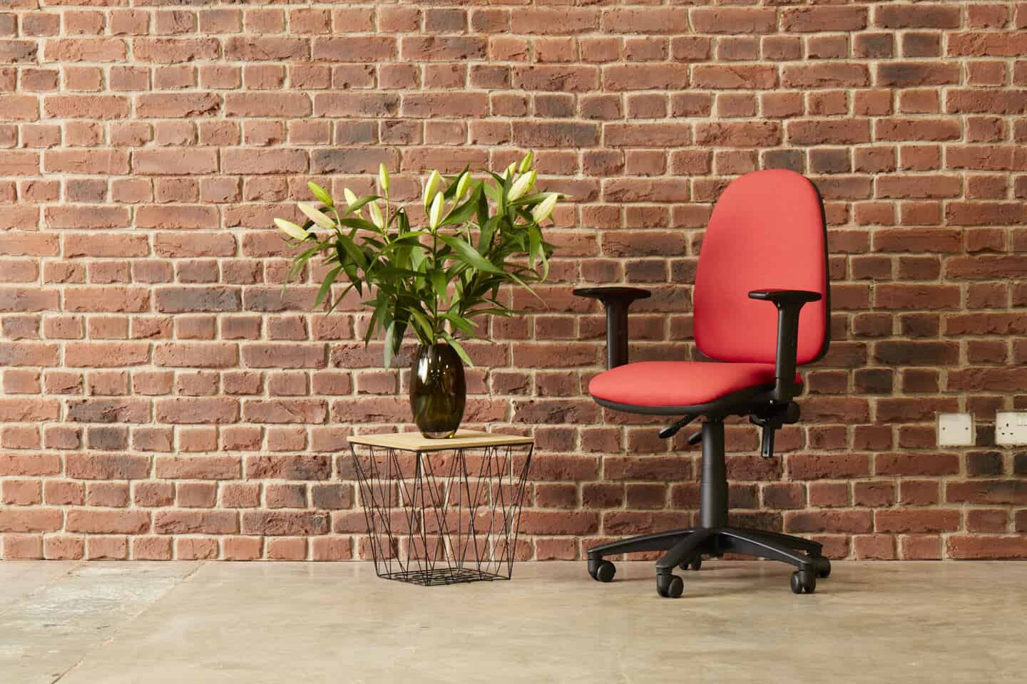 An ergonomic office chair infront of an exposed brick wall and next to a coffee table with a vase of flowers on it